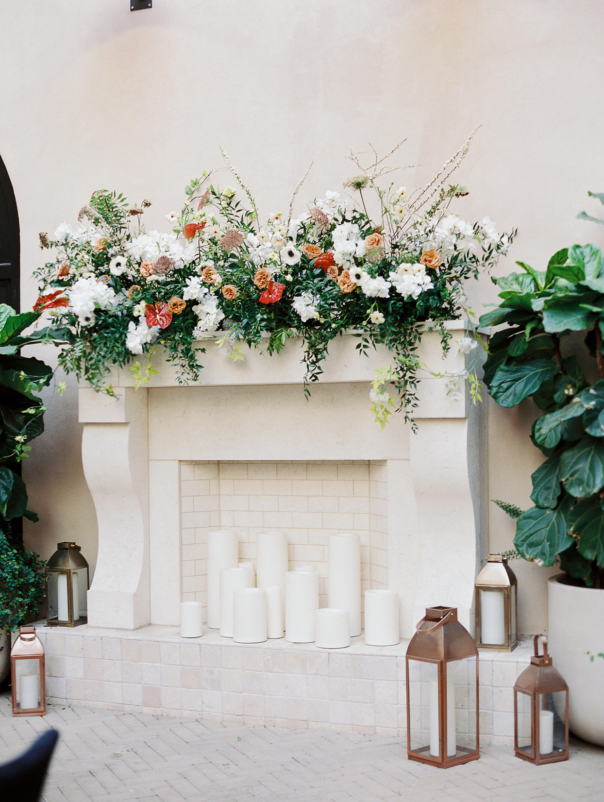 wedding reception mantel with poppies roses and anthurium flowers and white candles