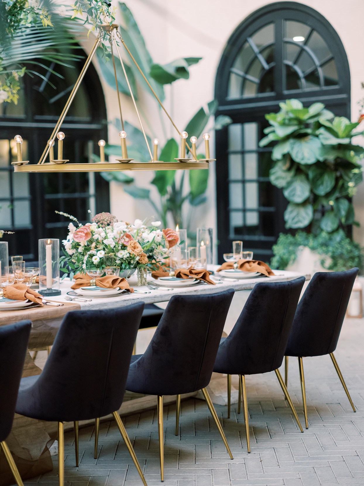 wedding reception tablescape with black velvet chairs and gold accents