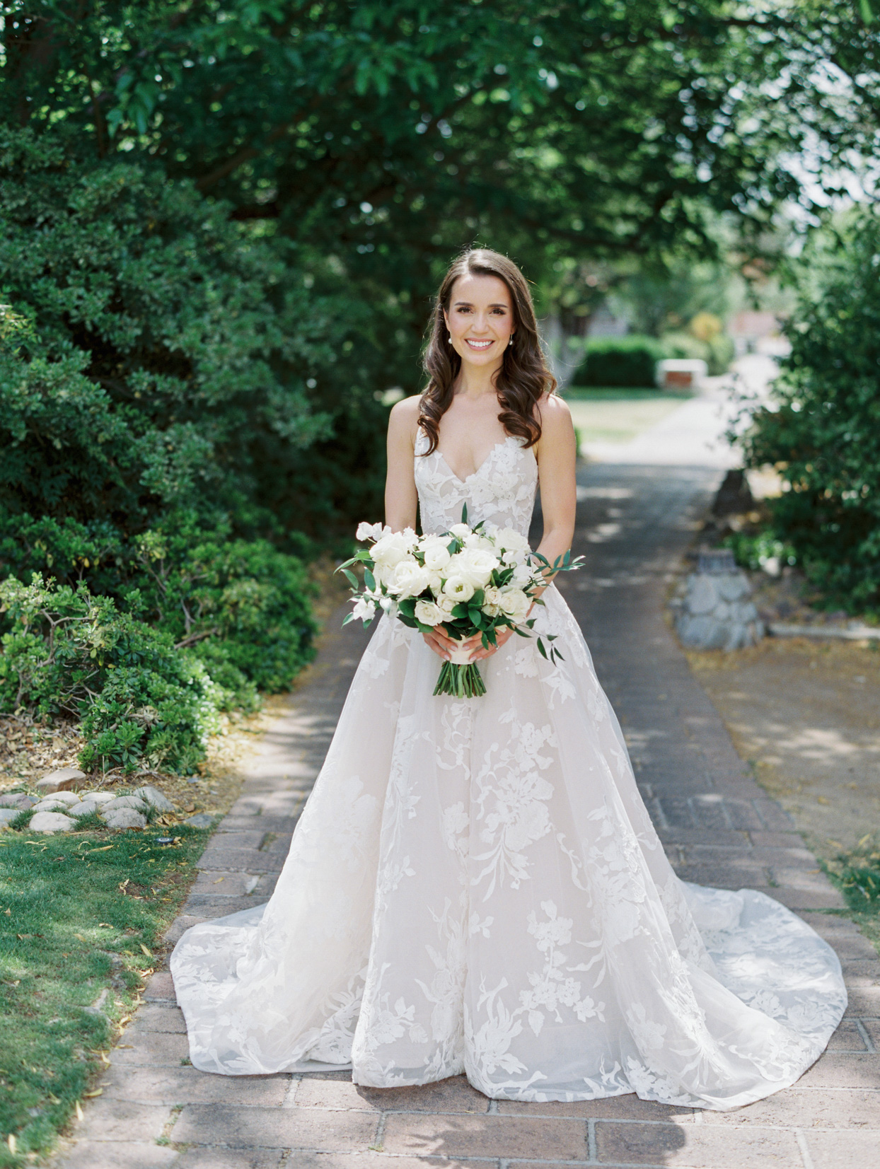 bride smiling wearing a-line dress holding white rose floral bouquet