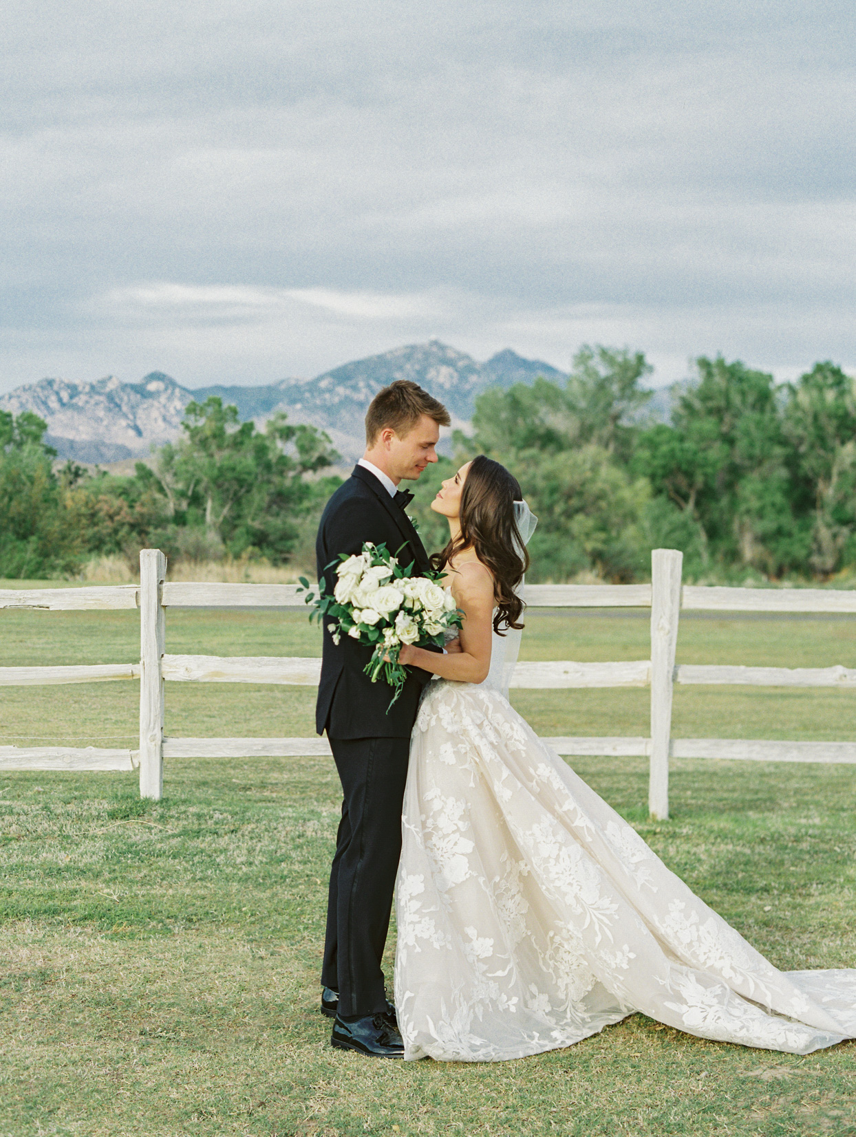 bride and groom look into each others eyes next to wooden fence outside