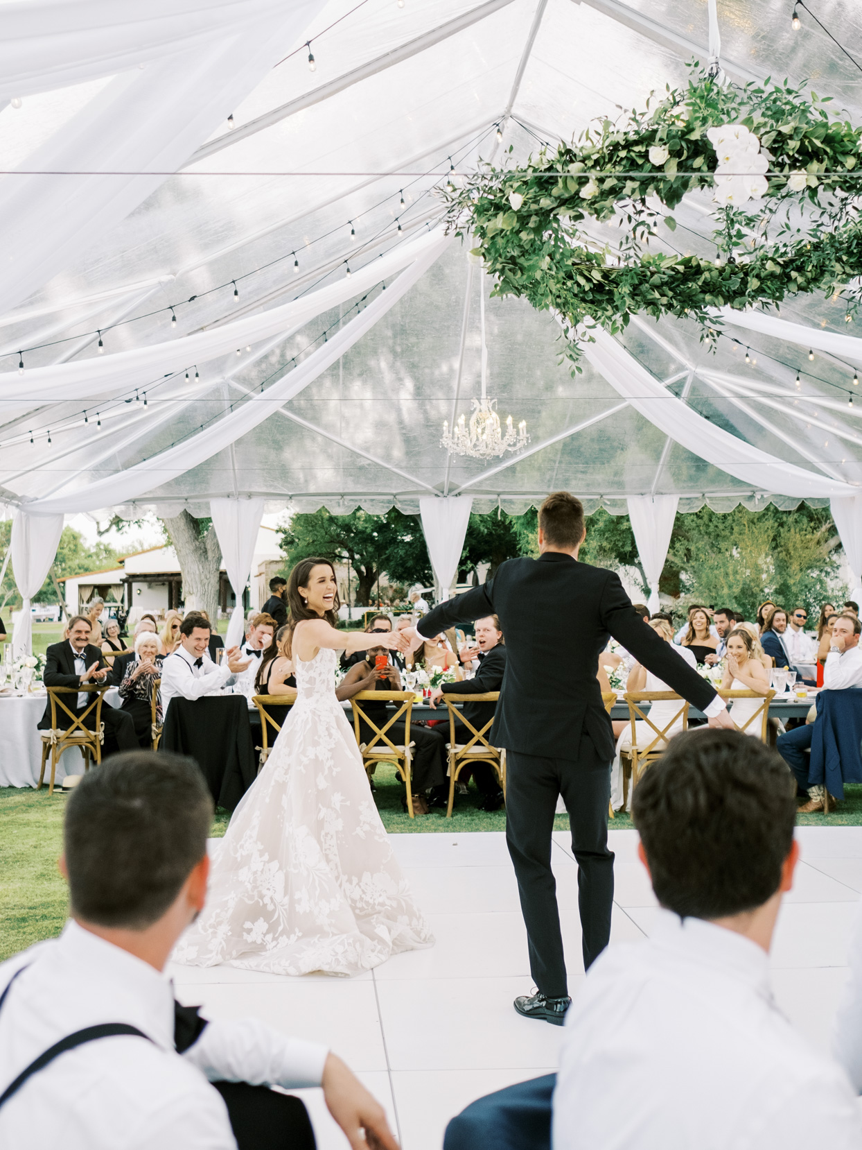 bride smiling holding grooms hand during first dance