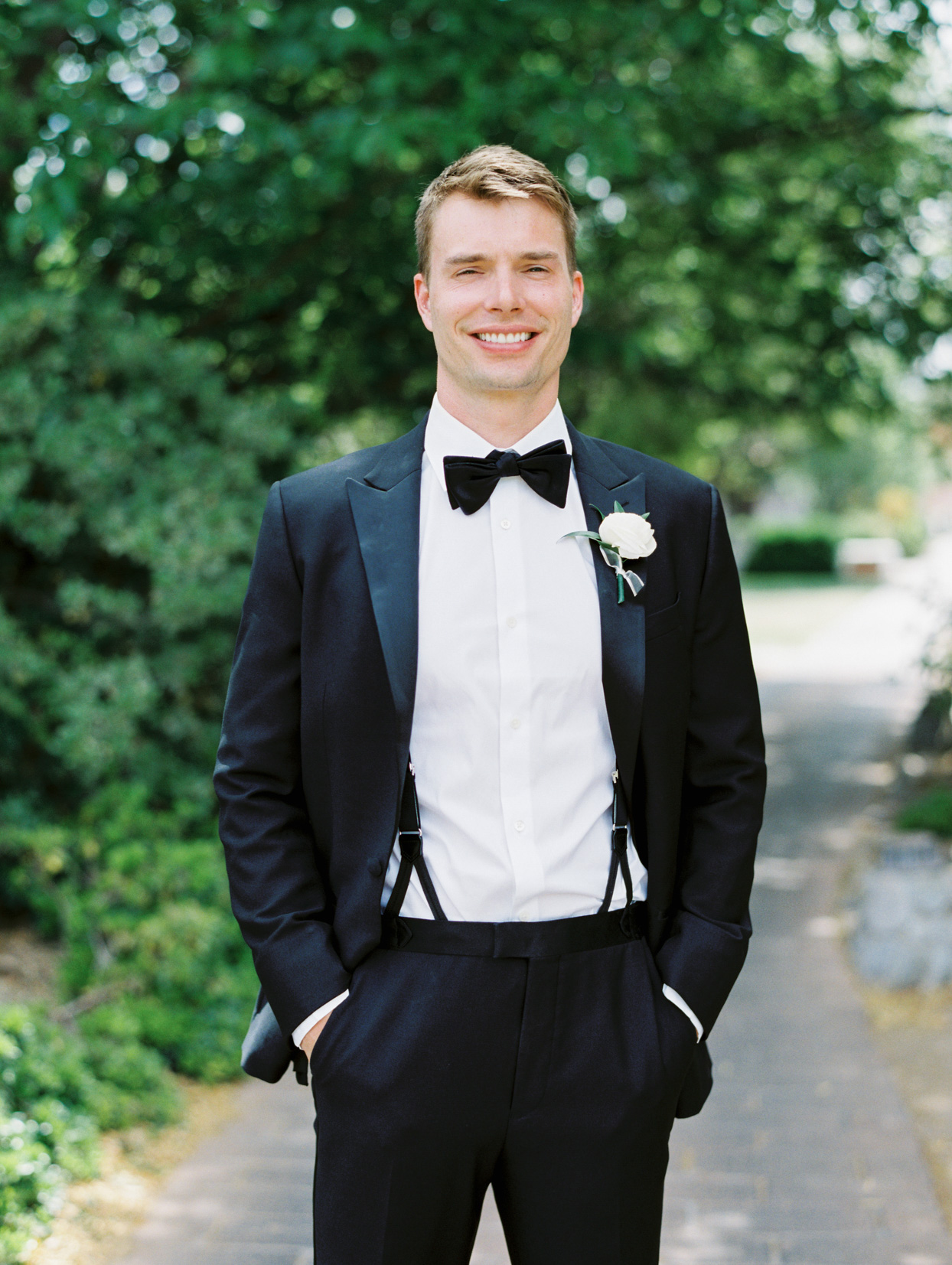 groom smiling wearing black and white suit