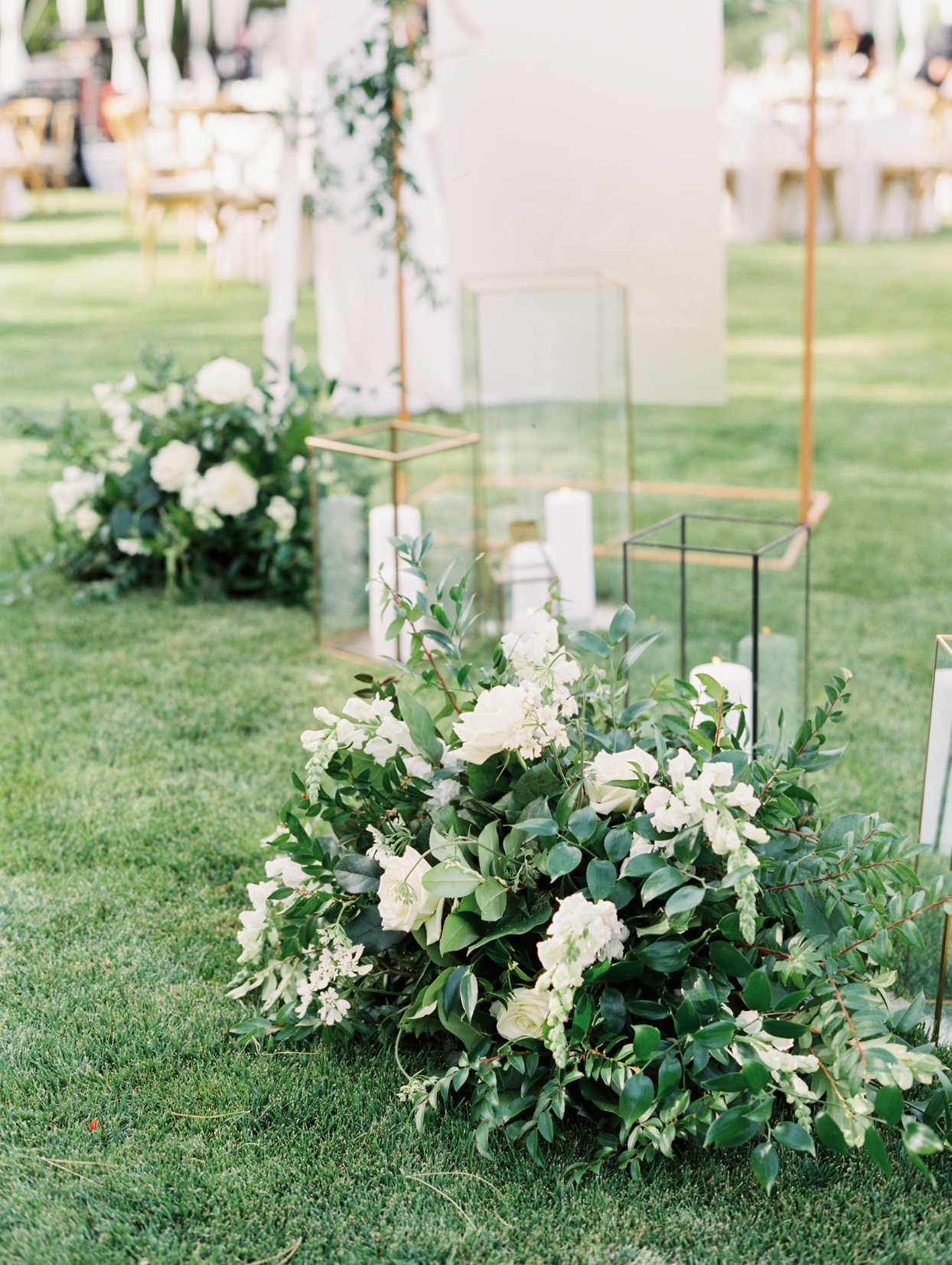 glass candle lanterns on grass with floral and greenery arrangements