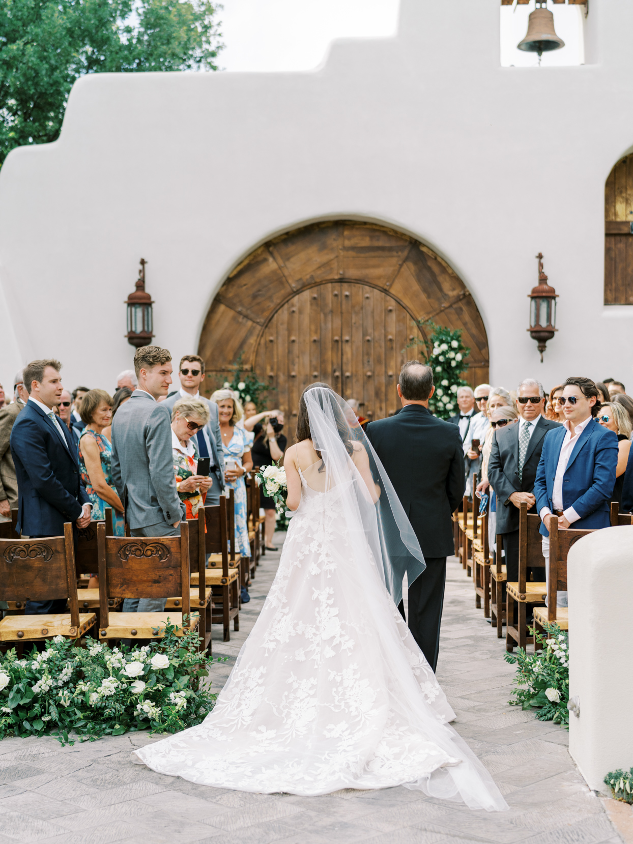 guests watch bride walk processional with father of bride