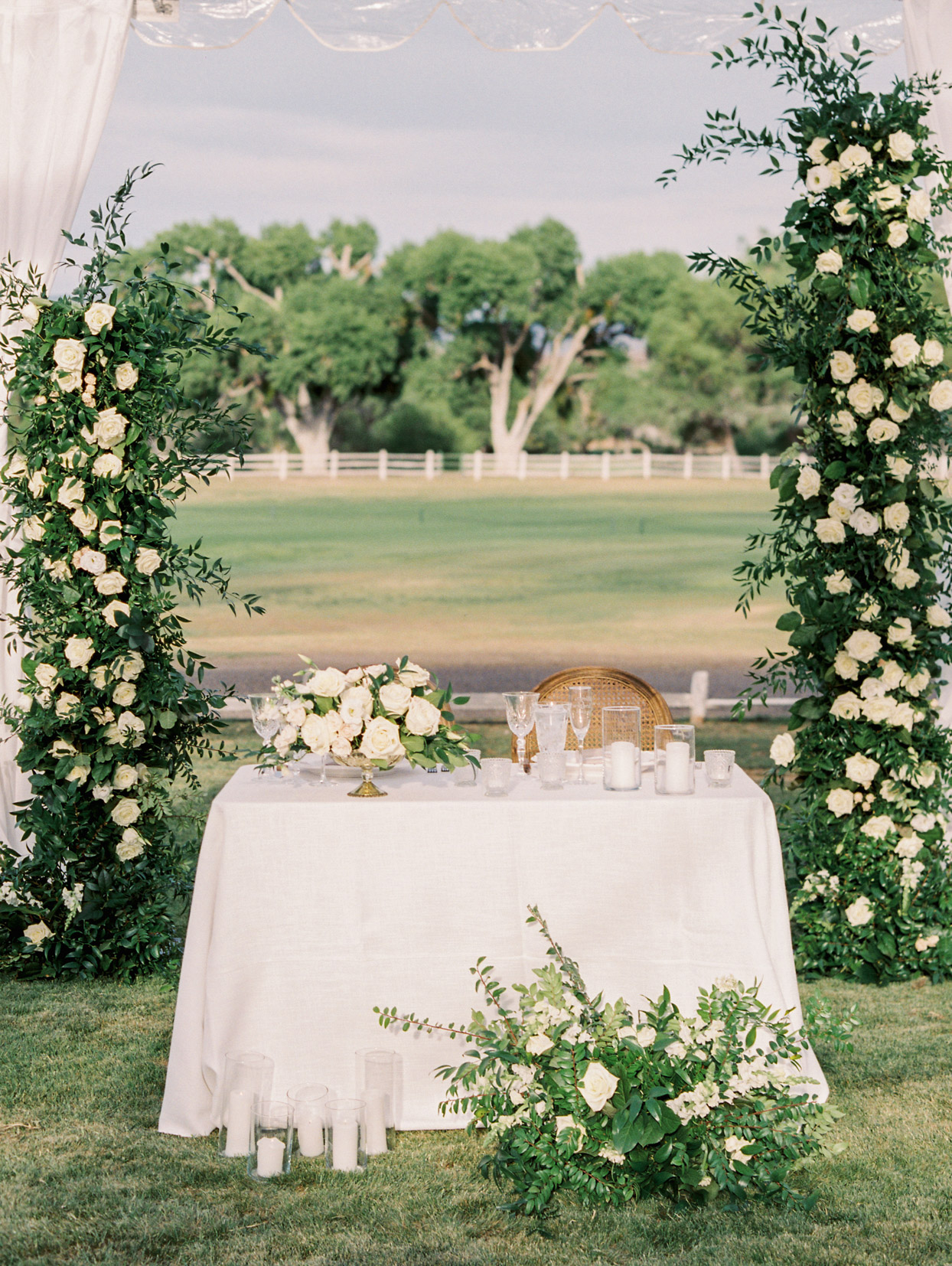 small white linen covered sweethearts table under floral arch
