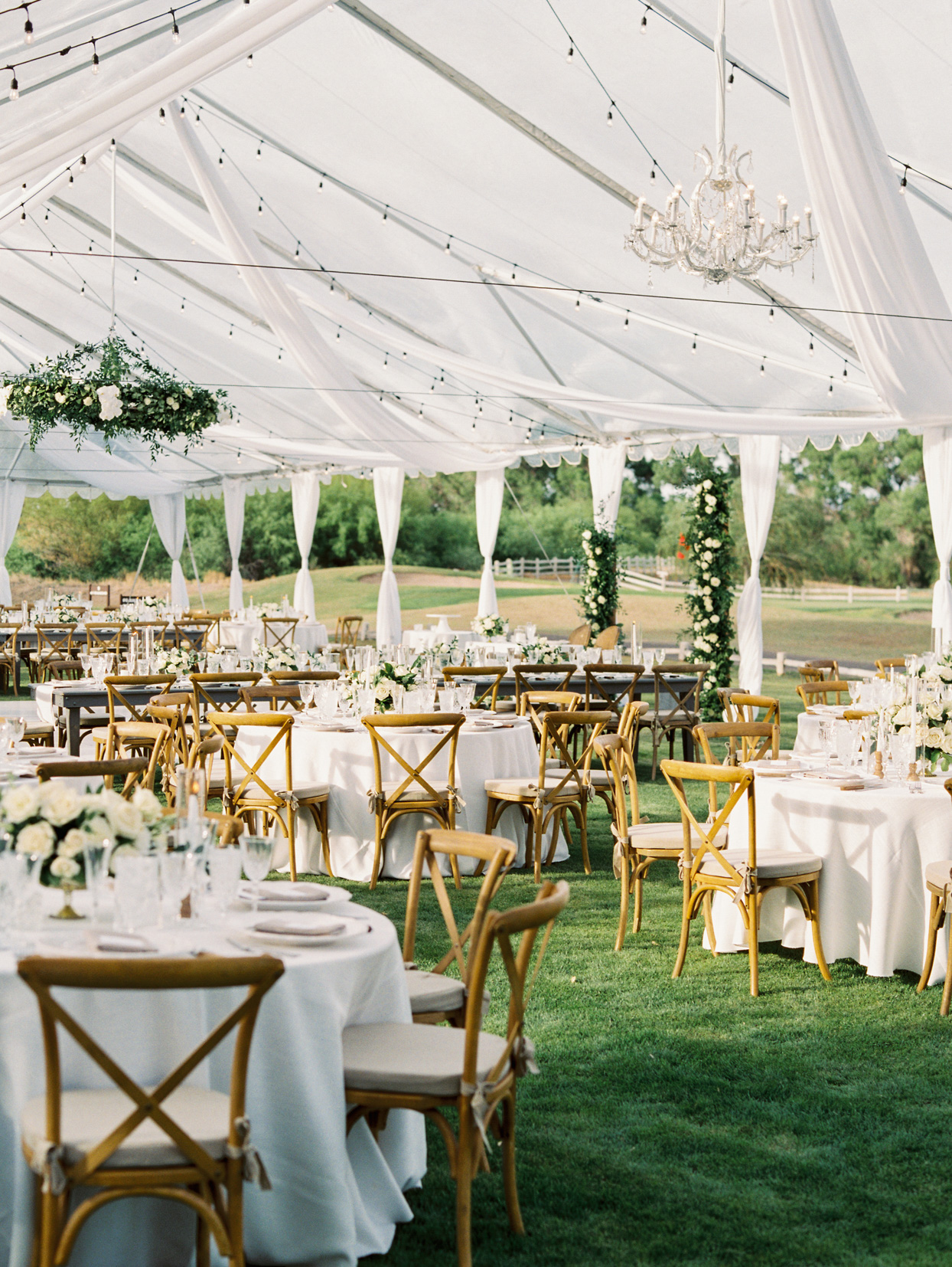 large white reception tent over white linen covered tables