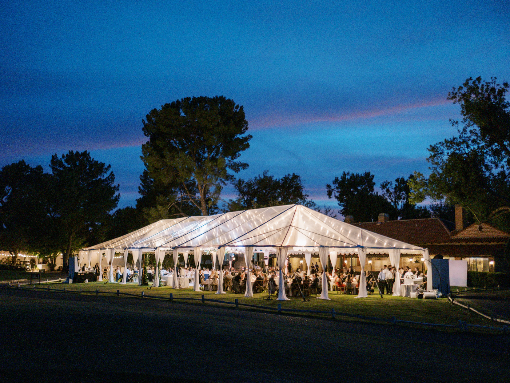 large white reception tent lit with string lights