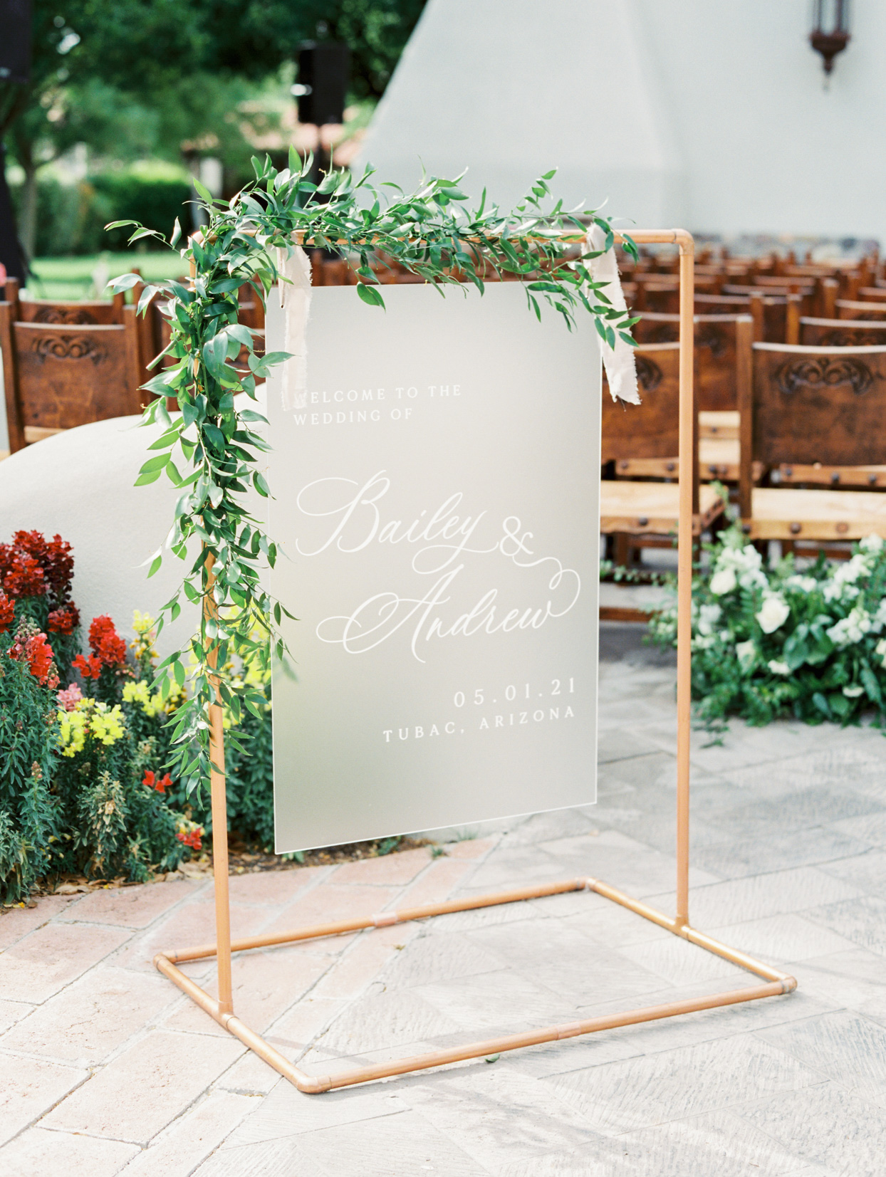 foggy white wedding sign hung on gold pipes with greenery decor