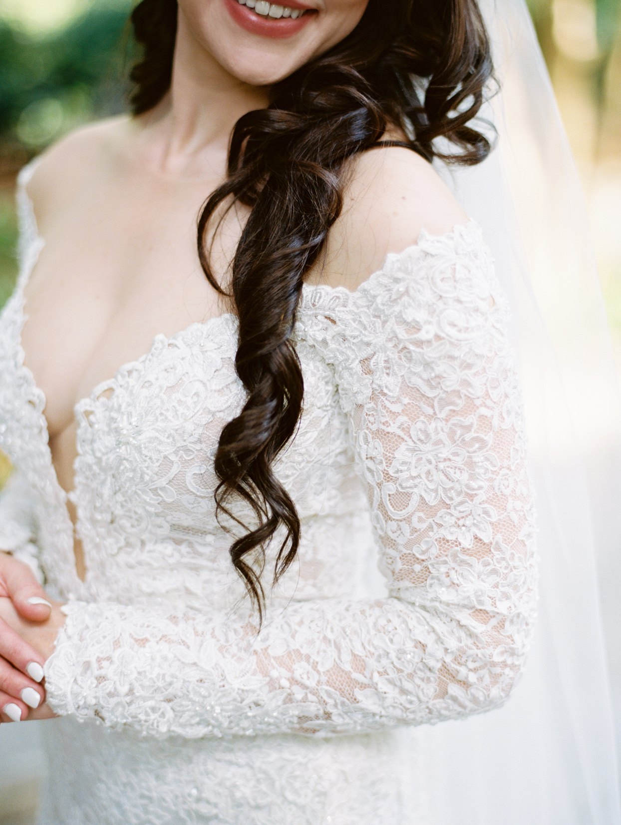 bride wearing gown with illusion neckline and lace sleeves