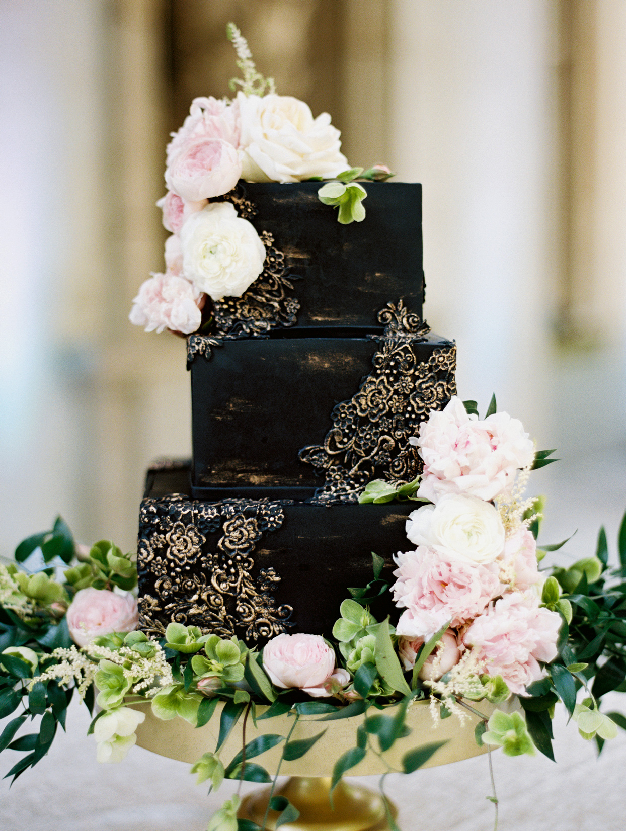 three-tiered square black wedding cake with gold-dusted lace pattern
