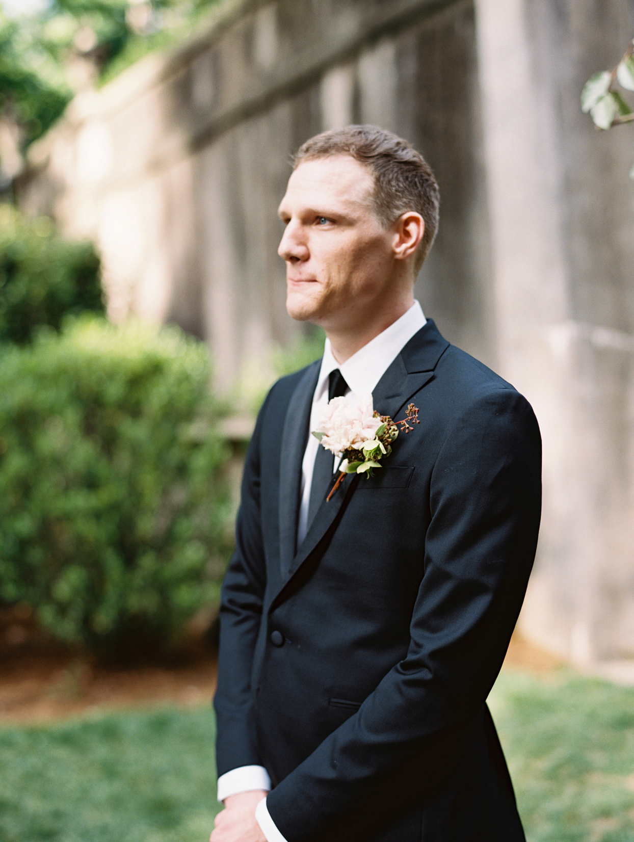 groom wearing peony with hellebores boutonniere