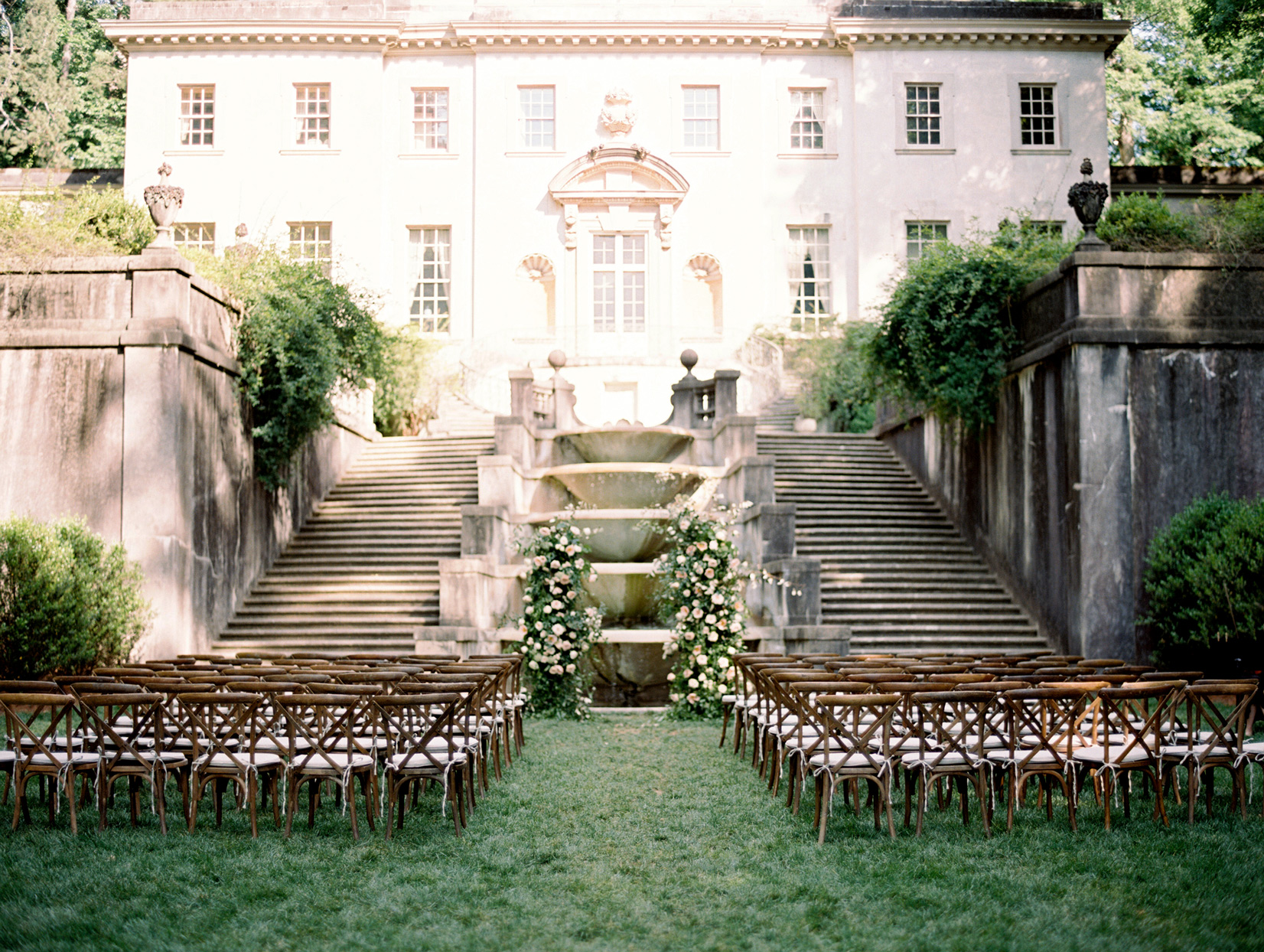 outdoor wedding ceremony setup stone staircases and draping greenery
