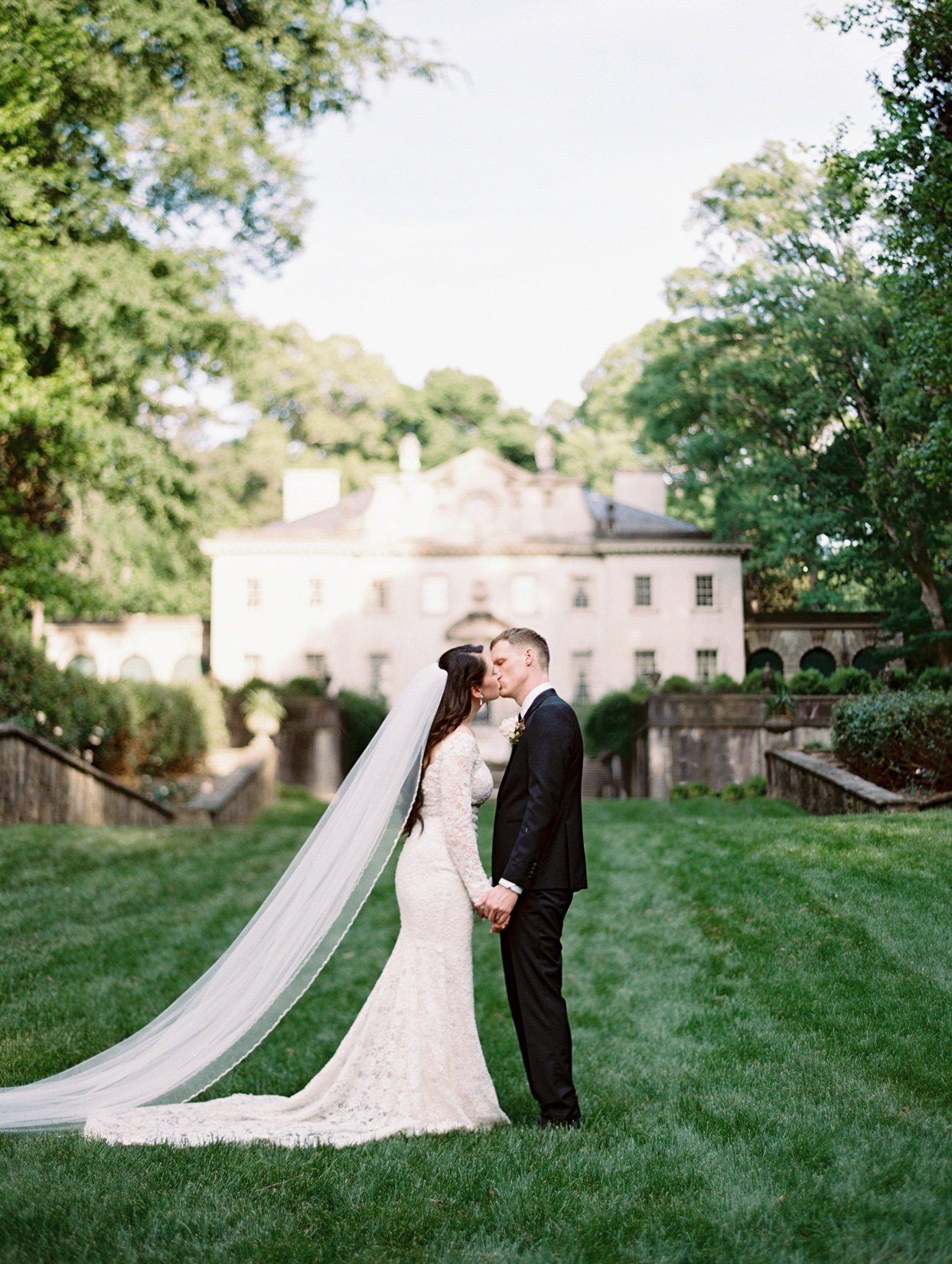 bride and groom holding hands kissing