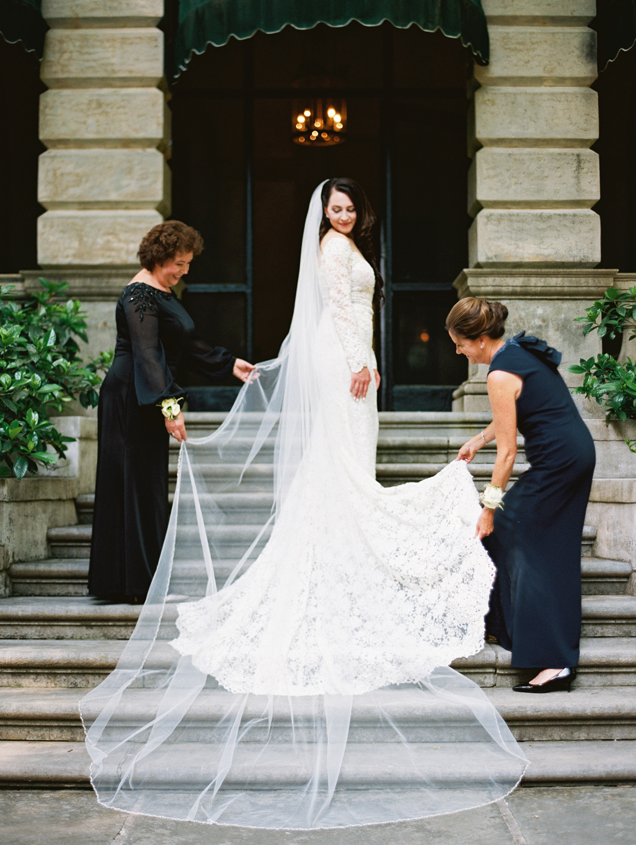 mother of the bride adjusting train of brides gown