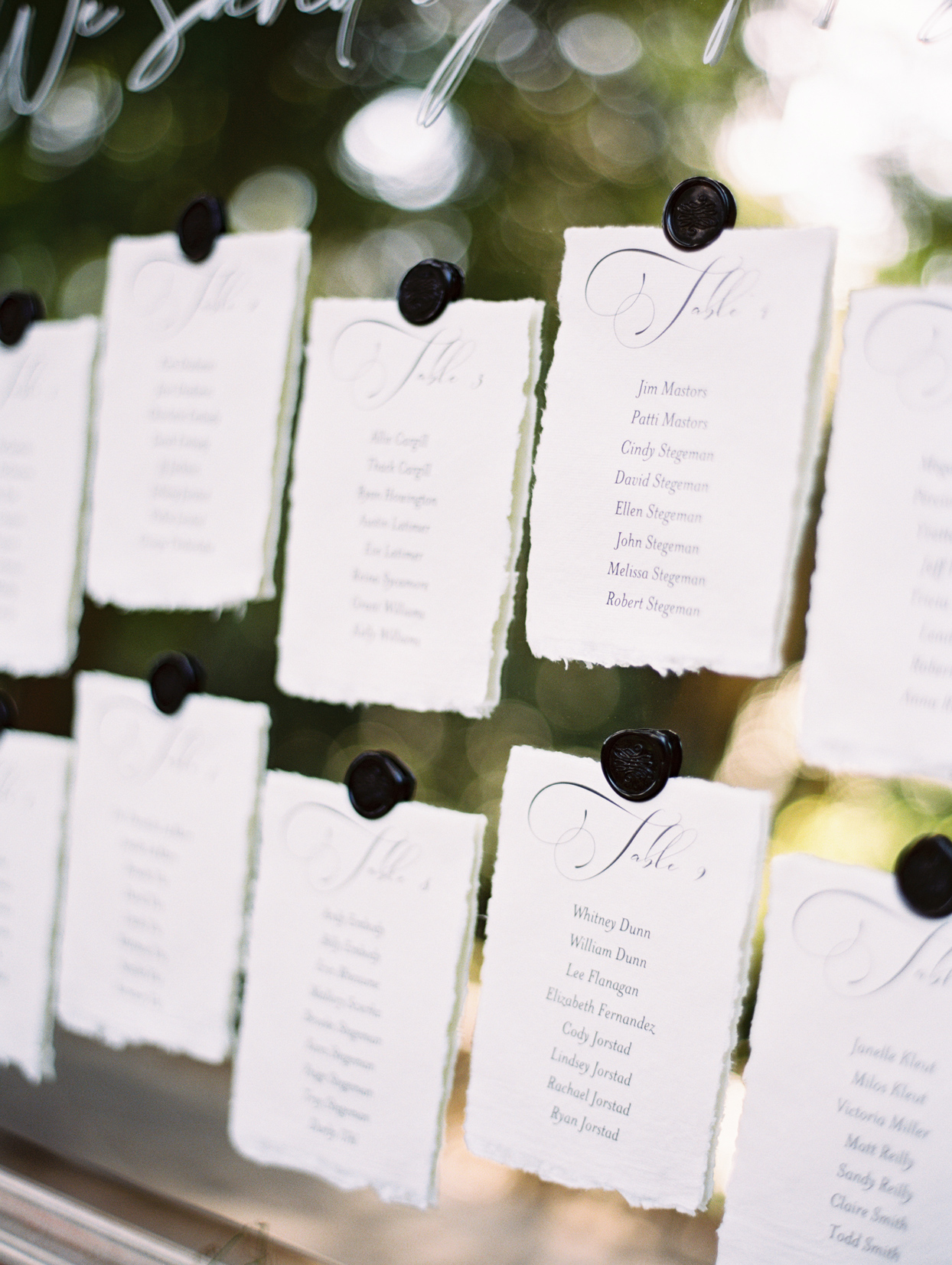 deckle-edge escort cards adhered to antique silver mirror