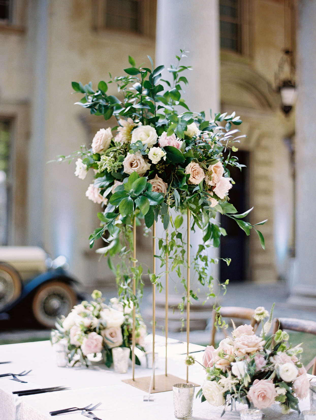 tall floral centerpieces on gold-framed stands