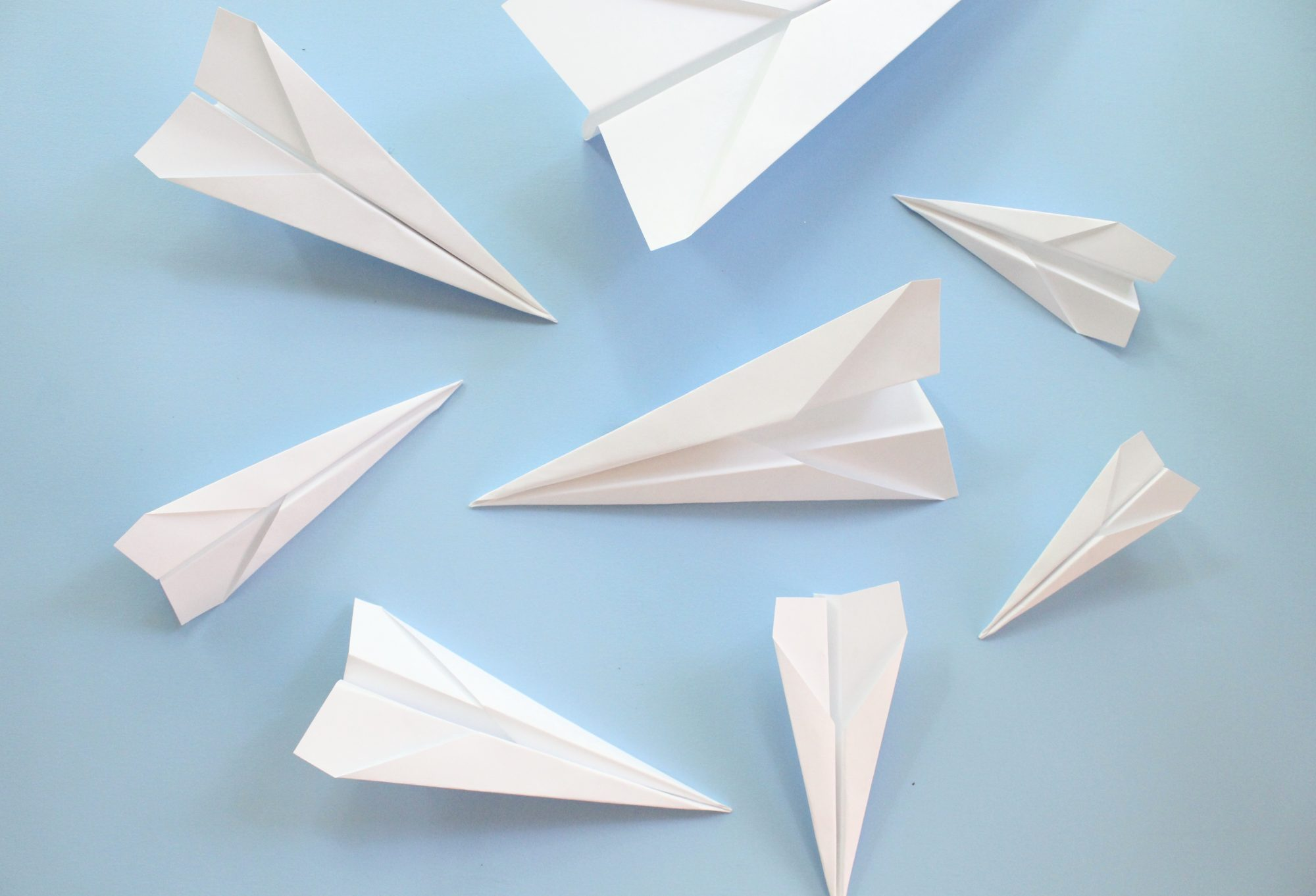 folded paper airplanes on blue surface