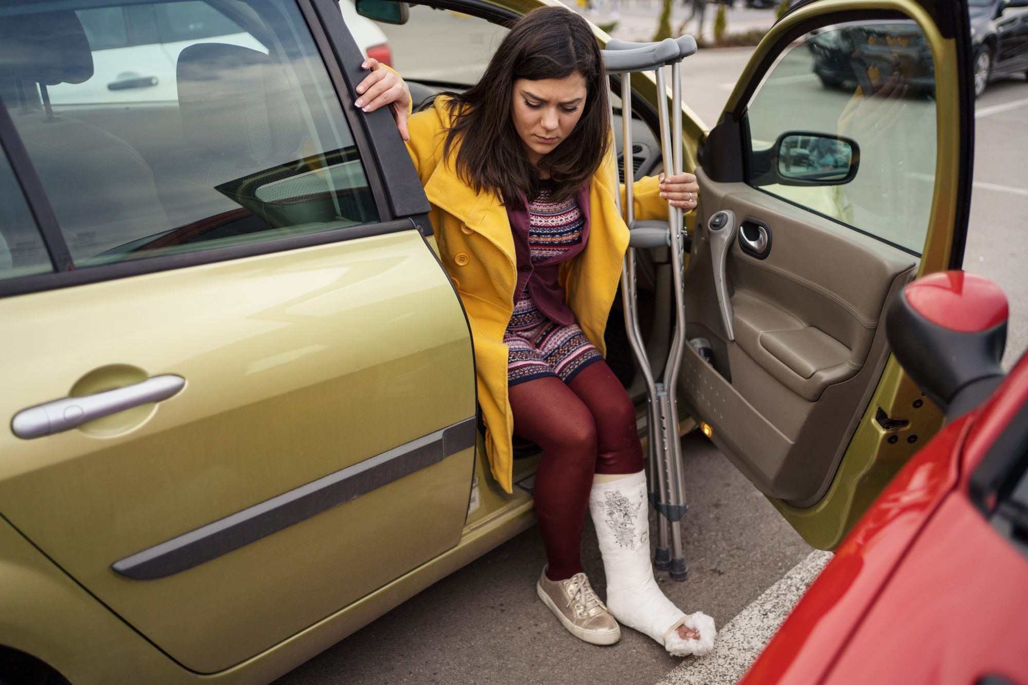 Woman with cast getting out of car