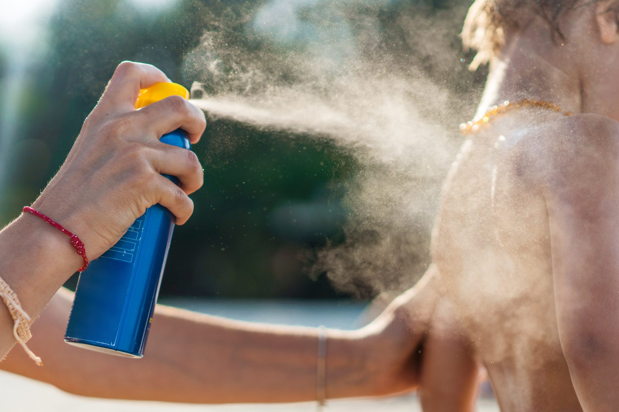 spraying sunscreen on child outdoors