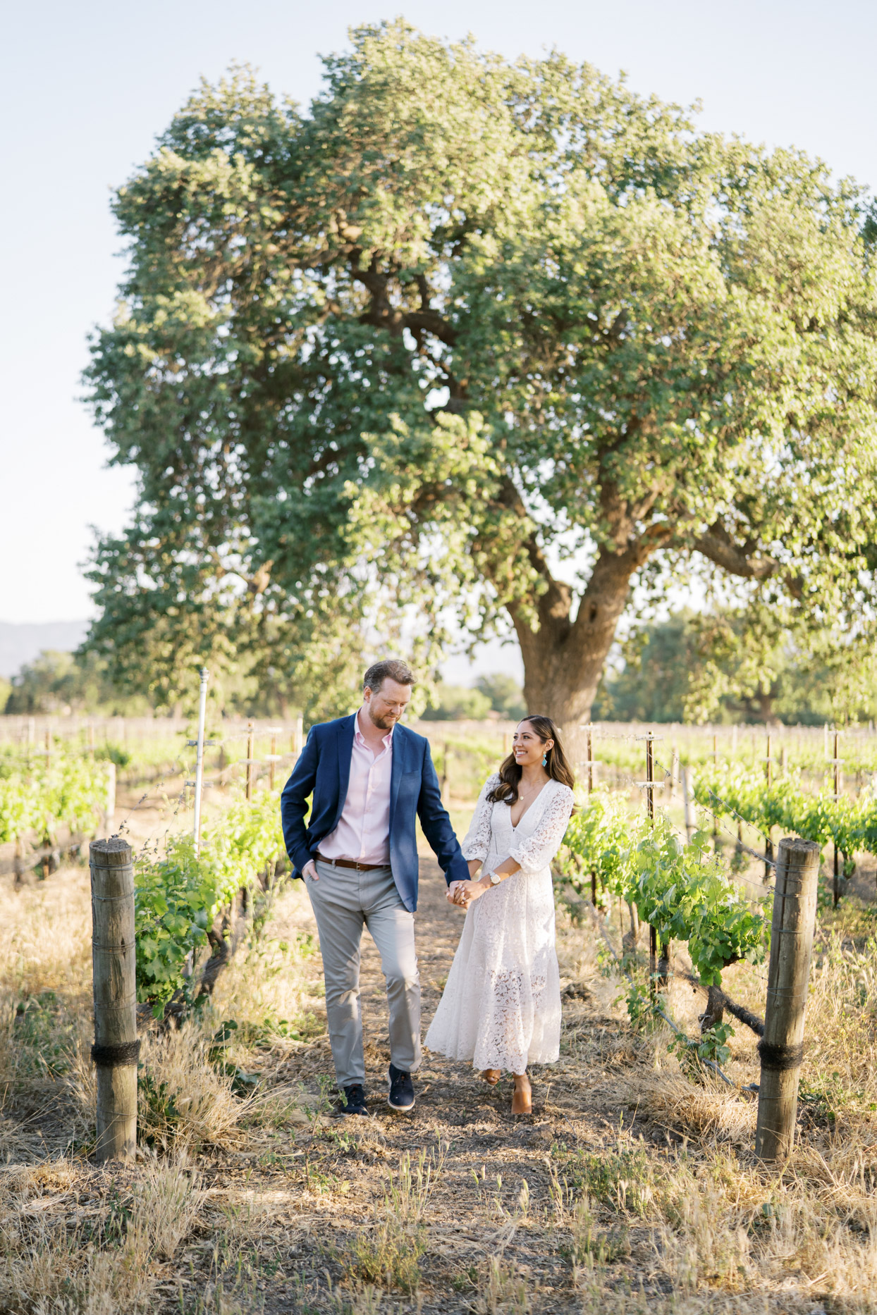 couple smiling holding hands in vineyard