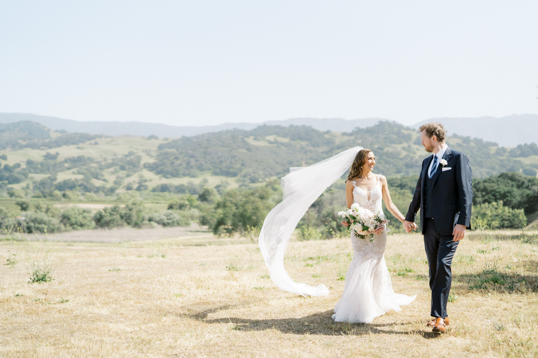 bride and groom smiling holding hands outside on hill