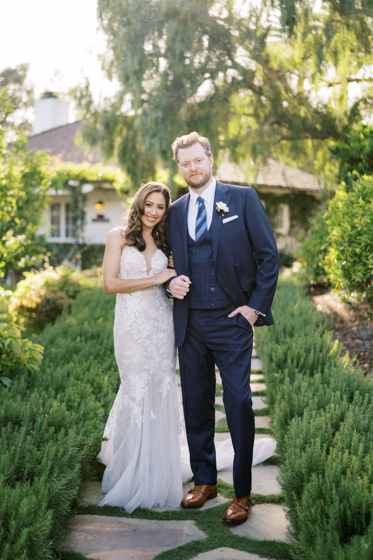 bride and groom smile for portrait on stone pathway