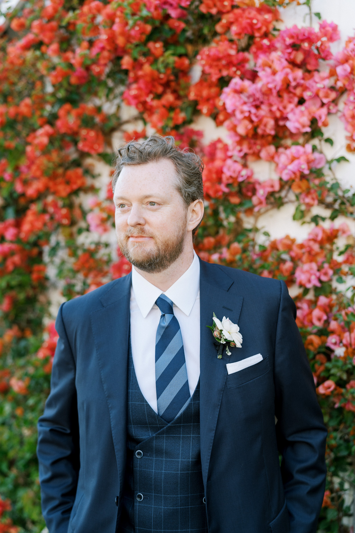 groom wearing navy blue suit in front of orange floral wall