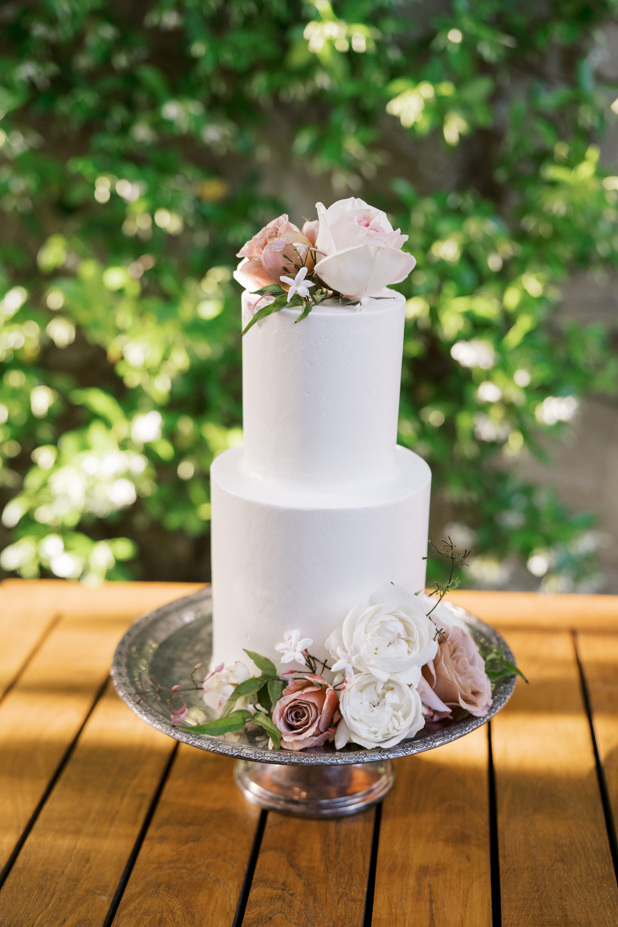 two tiered white wedding cake with white and blush flowers