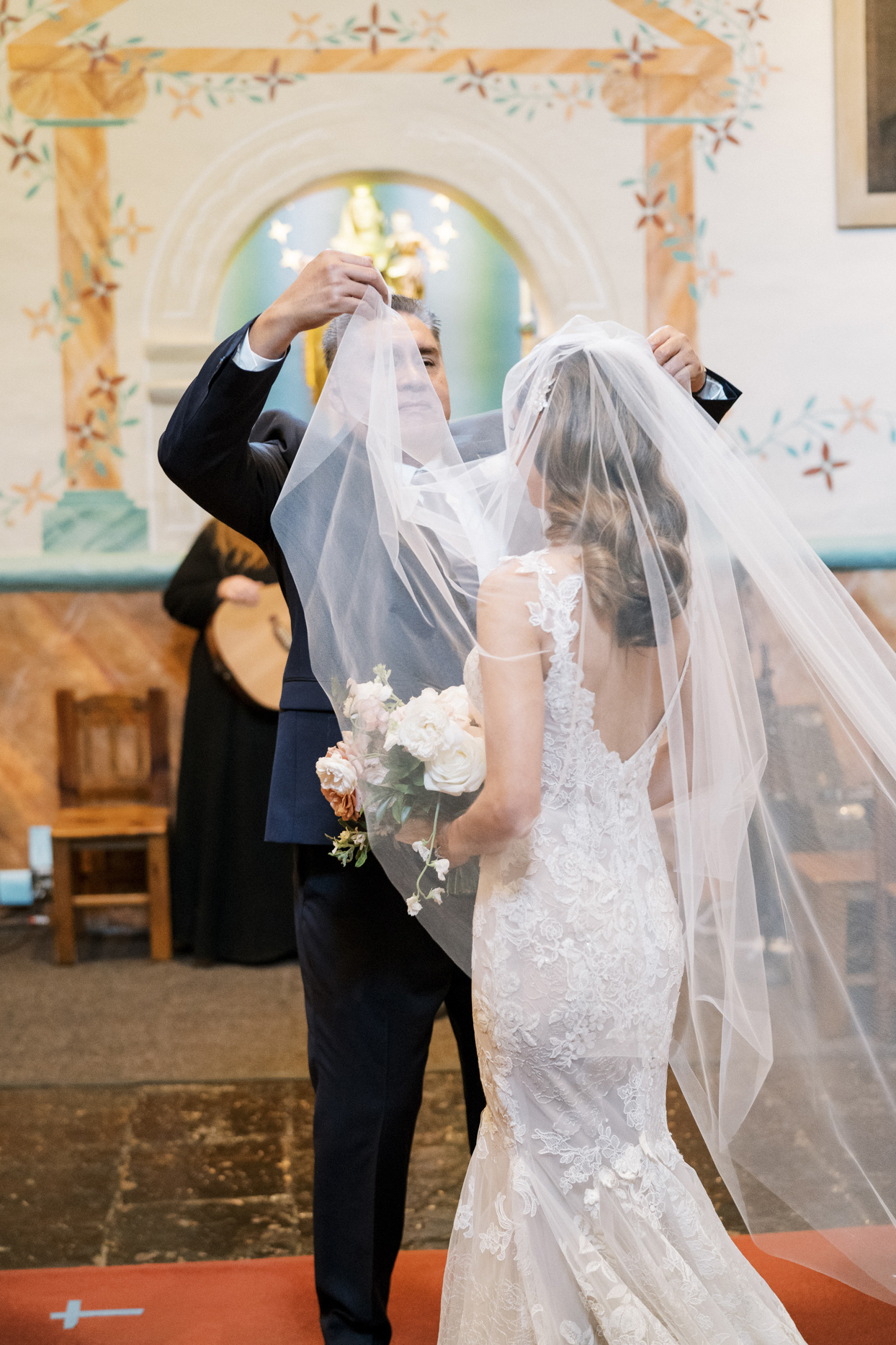 father of the bride lifting brides wedding veil