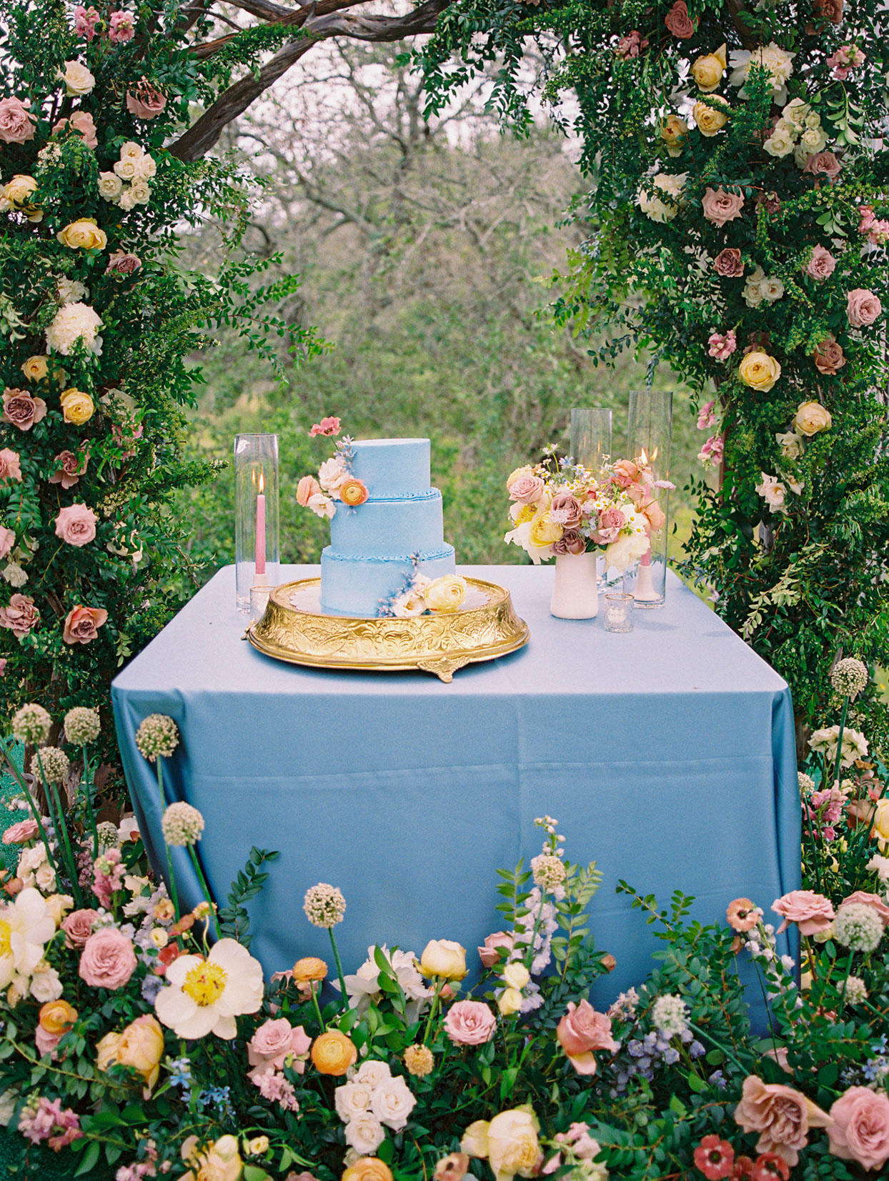 blue linen covered table with three tiered blue wedding cake