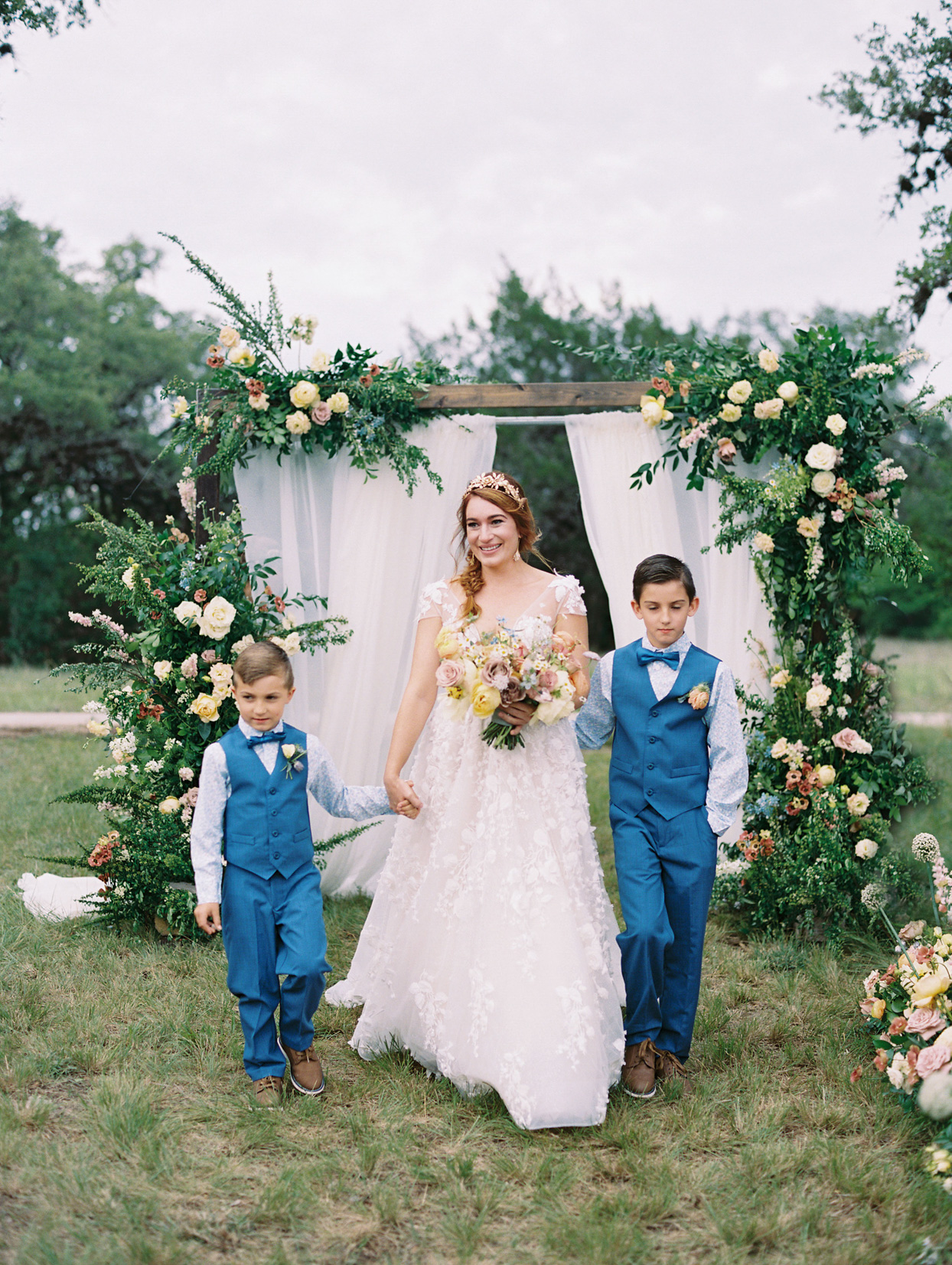 bride walking processional with two young boys