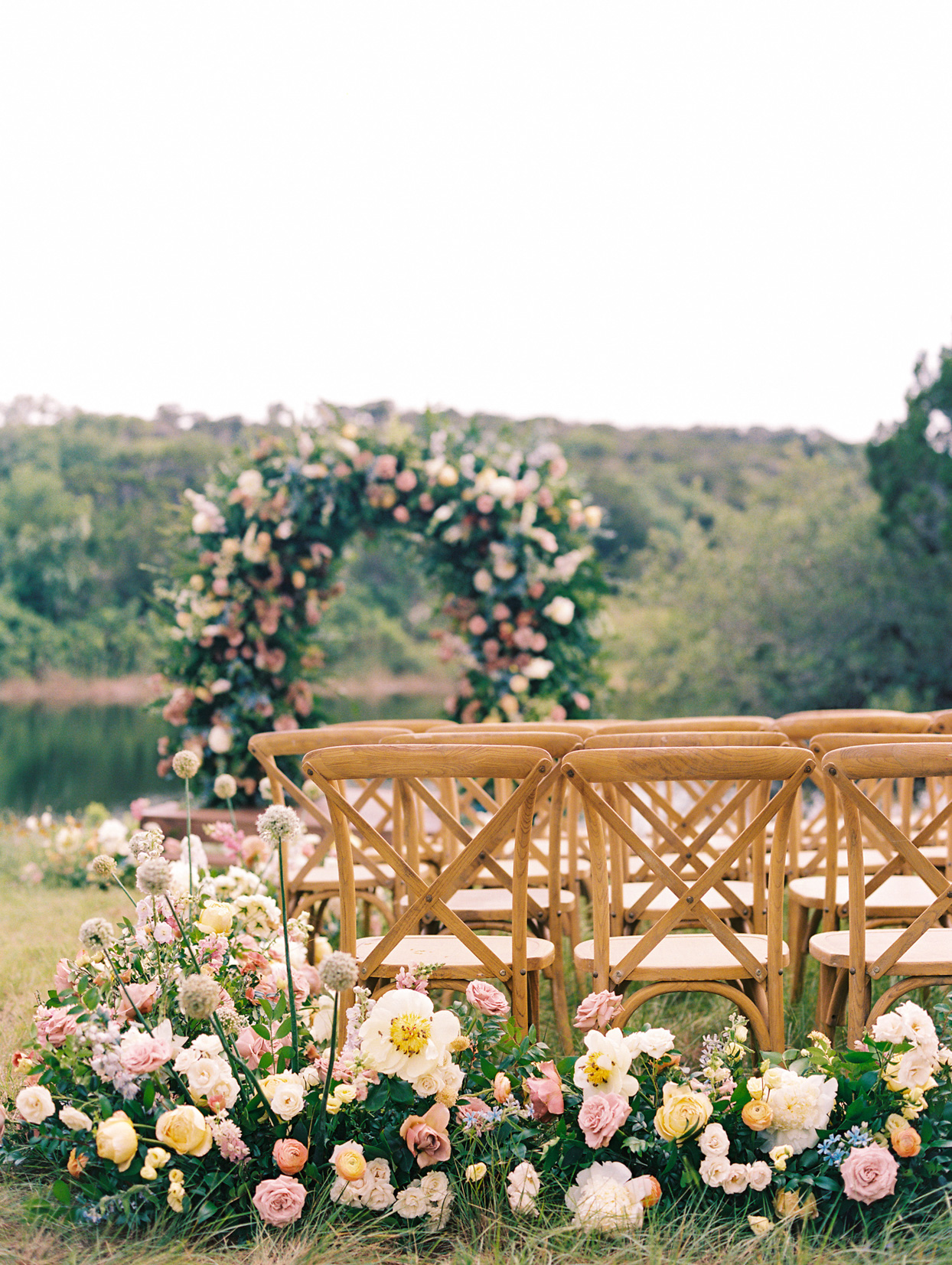 light wooden chairs wedding ceremony floral decor