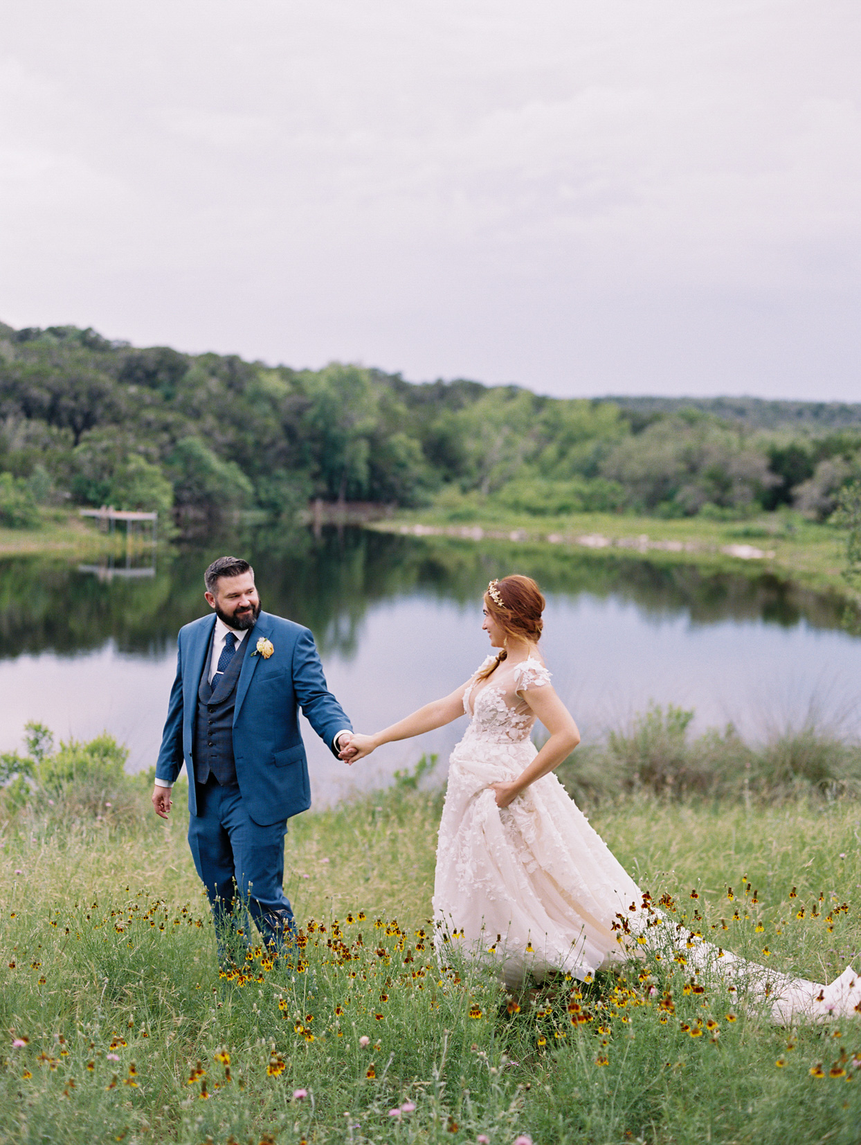 bride and groom smiling by lakeside