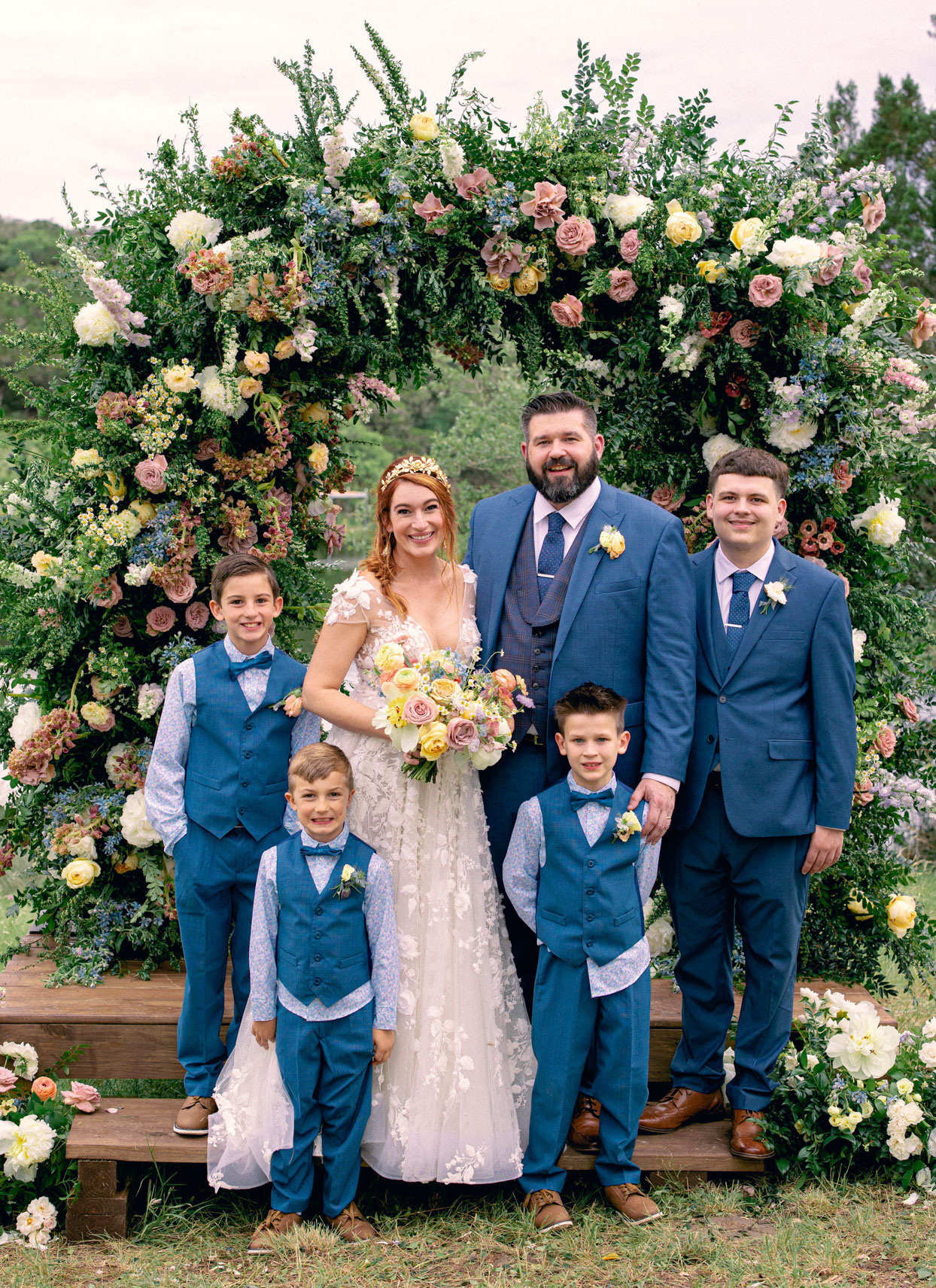 bride and groom under floral wedding arch with four sons