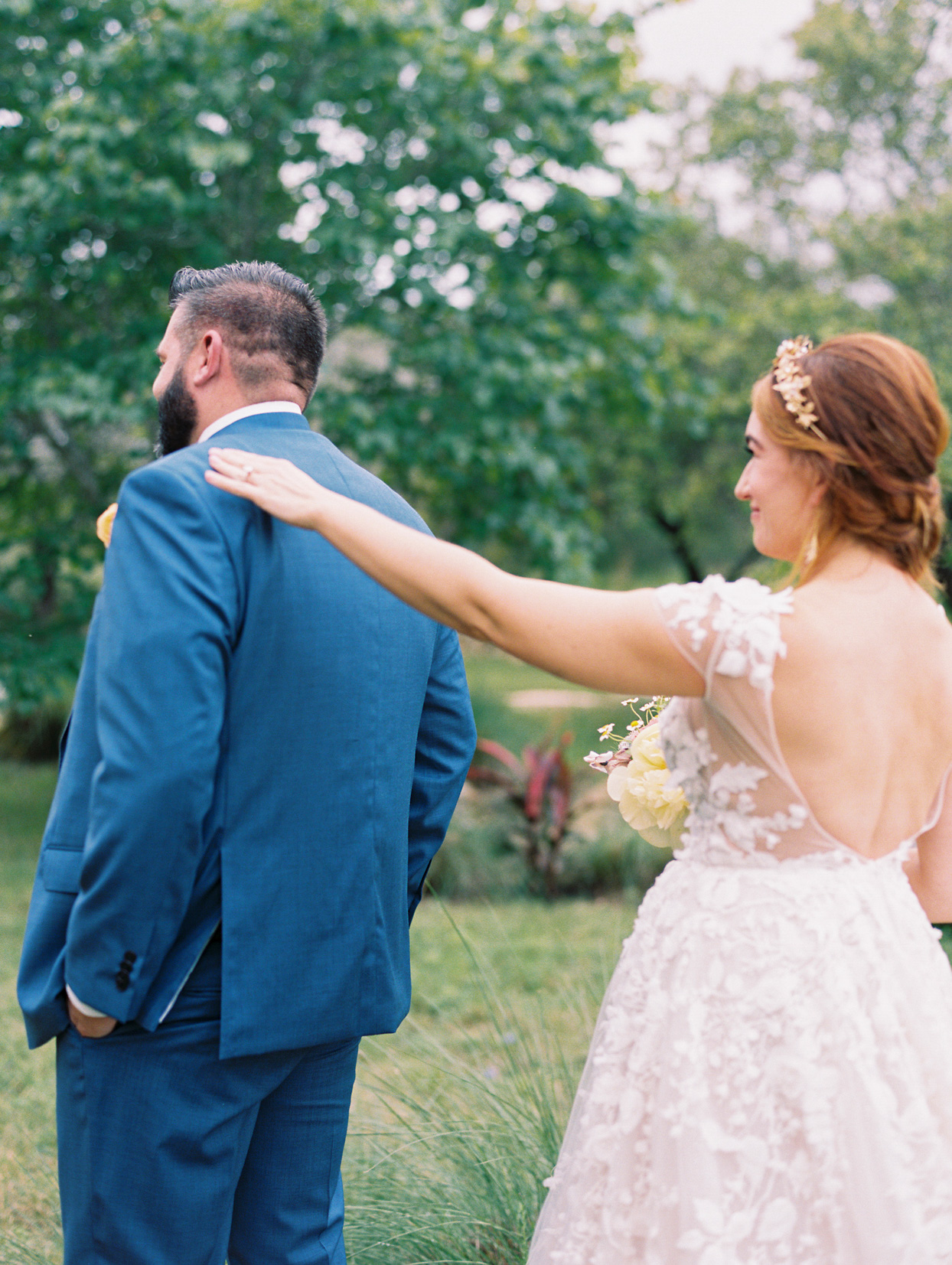 bride tapping groom on the shoulder for first look