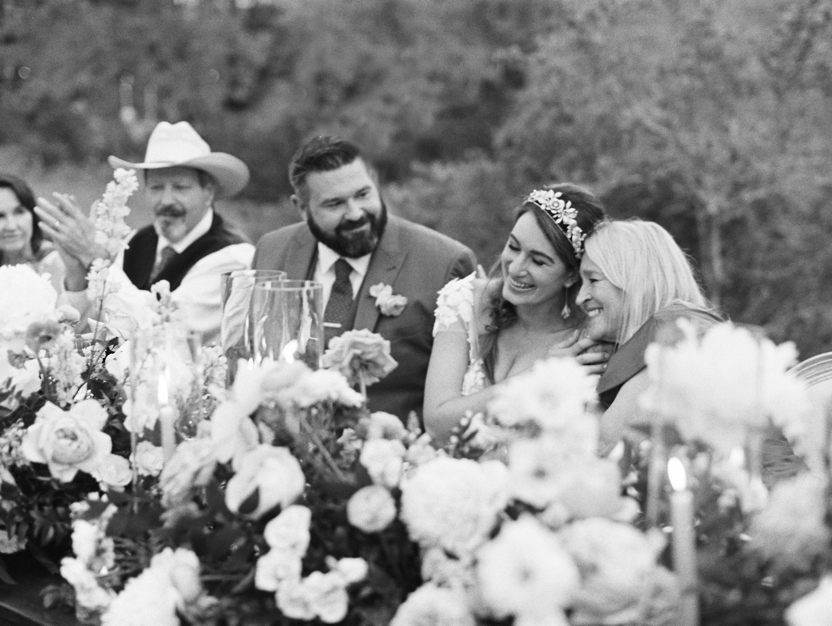 bride and groom smiling with family during reception