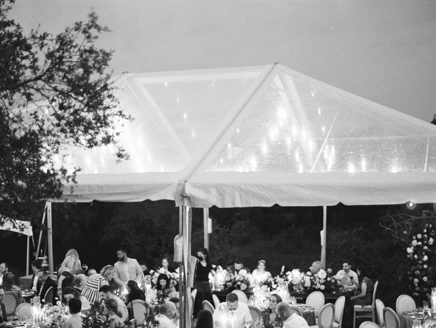 wedding guests under large white reception tent