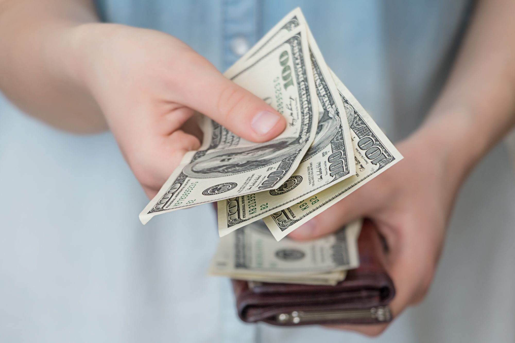 Midsection Of Woman Giving money From Wallet