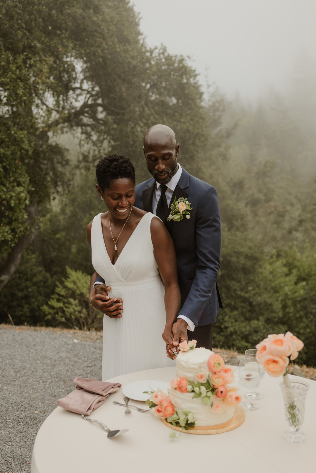 bride and groom cutting cake with foggy forest background