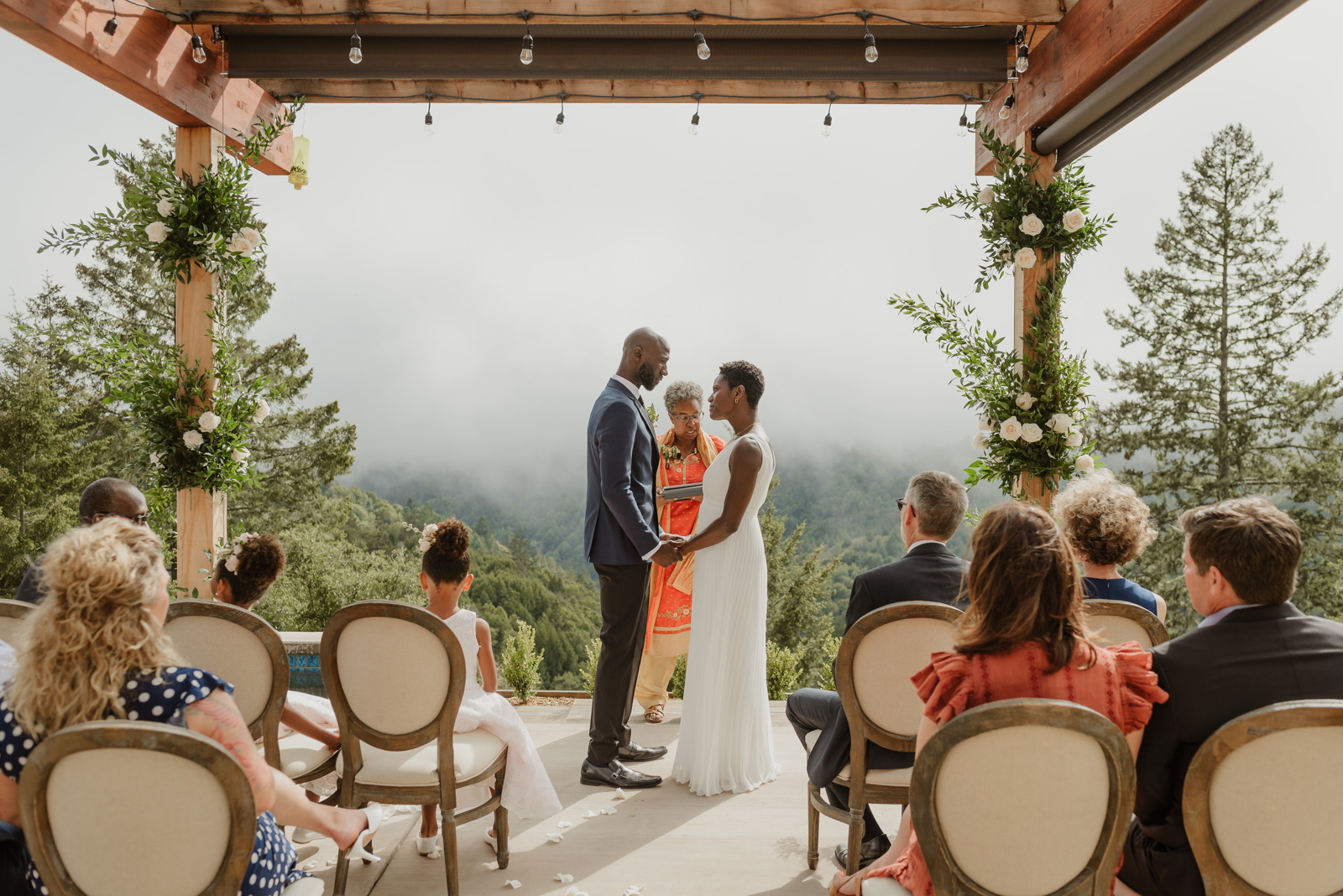 bride and groom holding hands for outdoor foggy ceremony