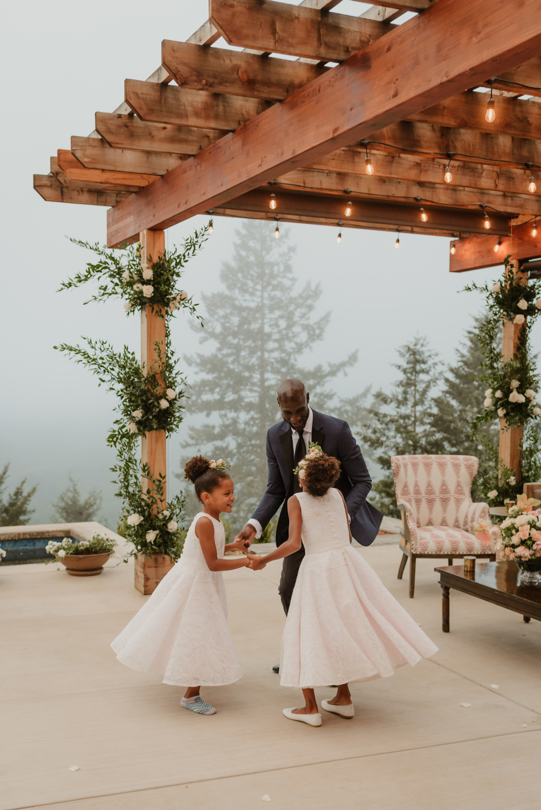 groom dancing with daughters at wedding