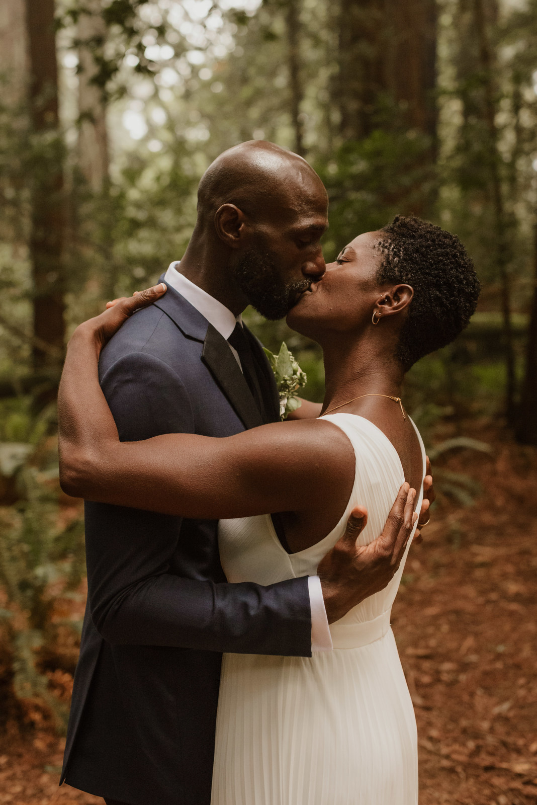couple kissing in forest for wedding portrait