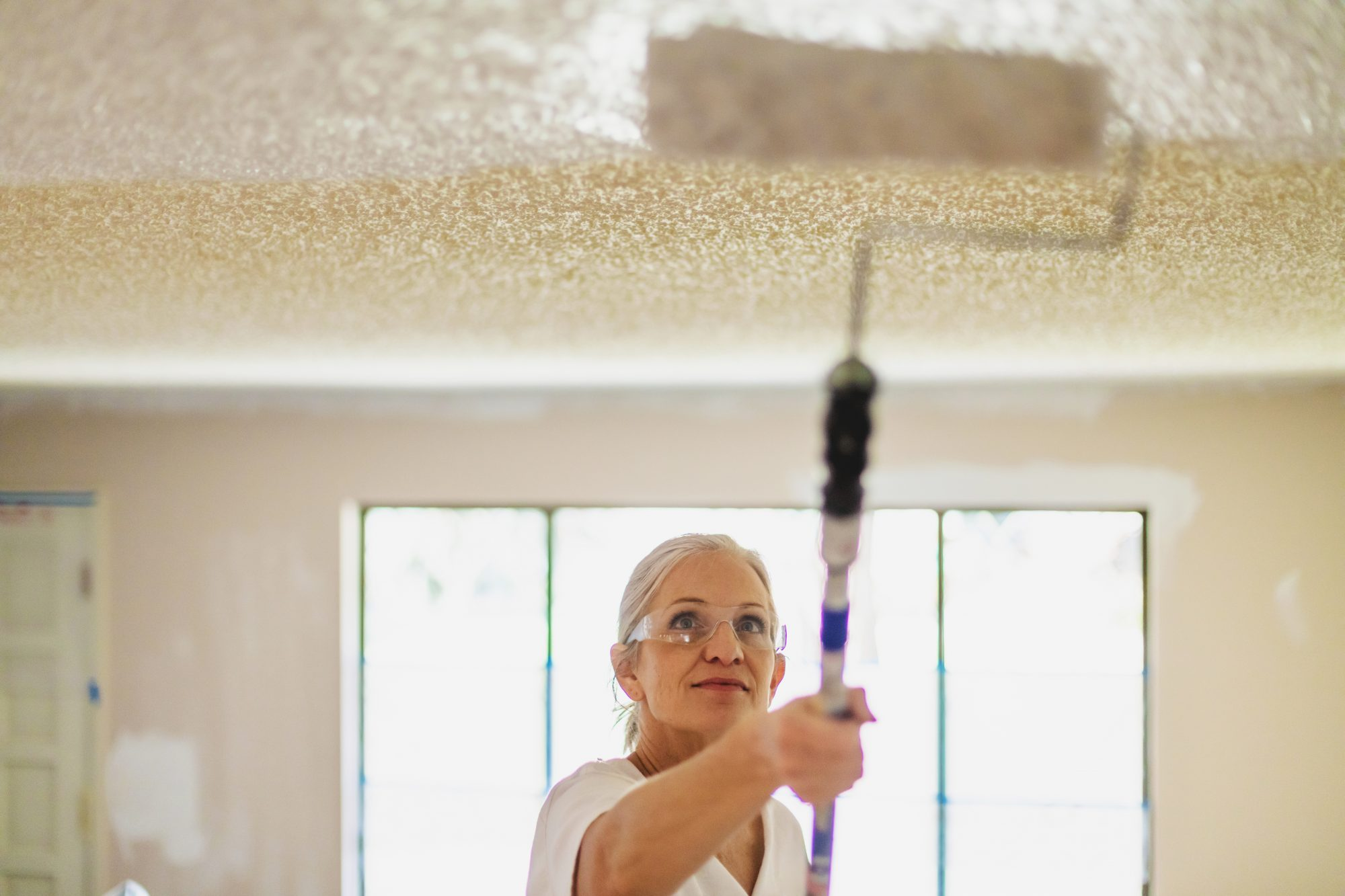 woman painting ceiling with roller brush