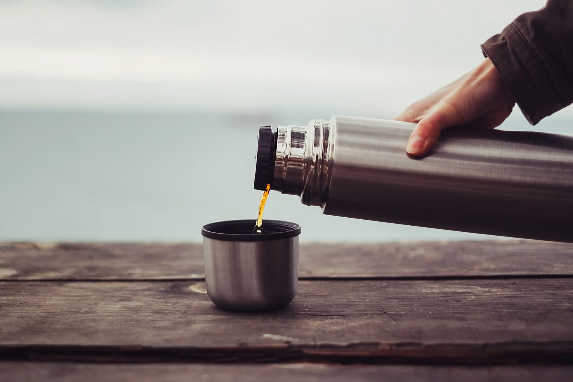 pouring hot coffee from thermos outdoors