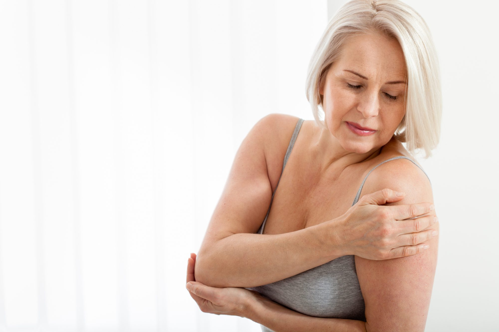 mature woman touching back of arms