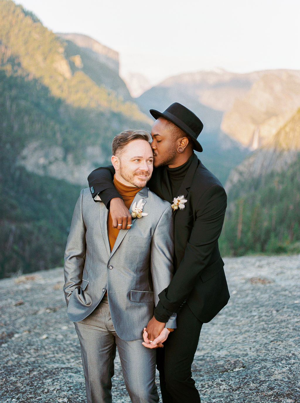 grooms embracing near mountains