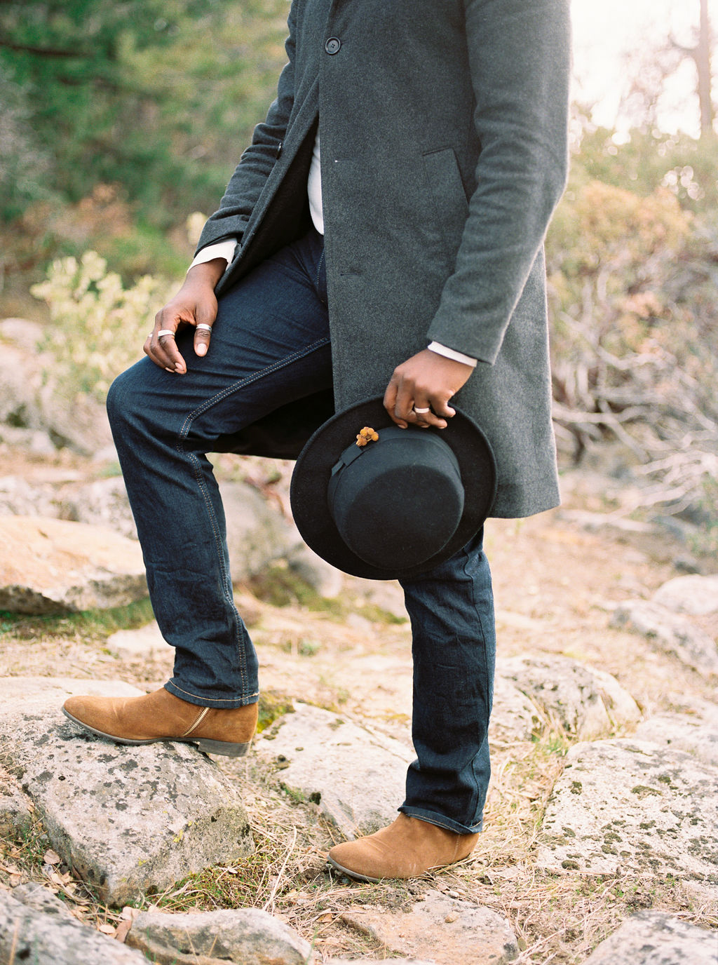 groom in jeans, hat, and coat
