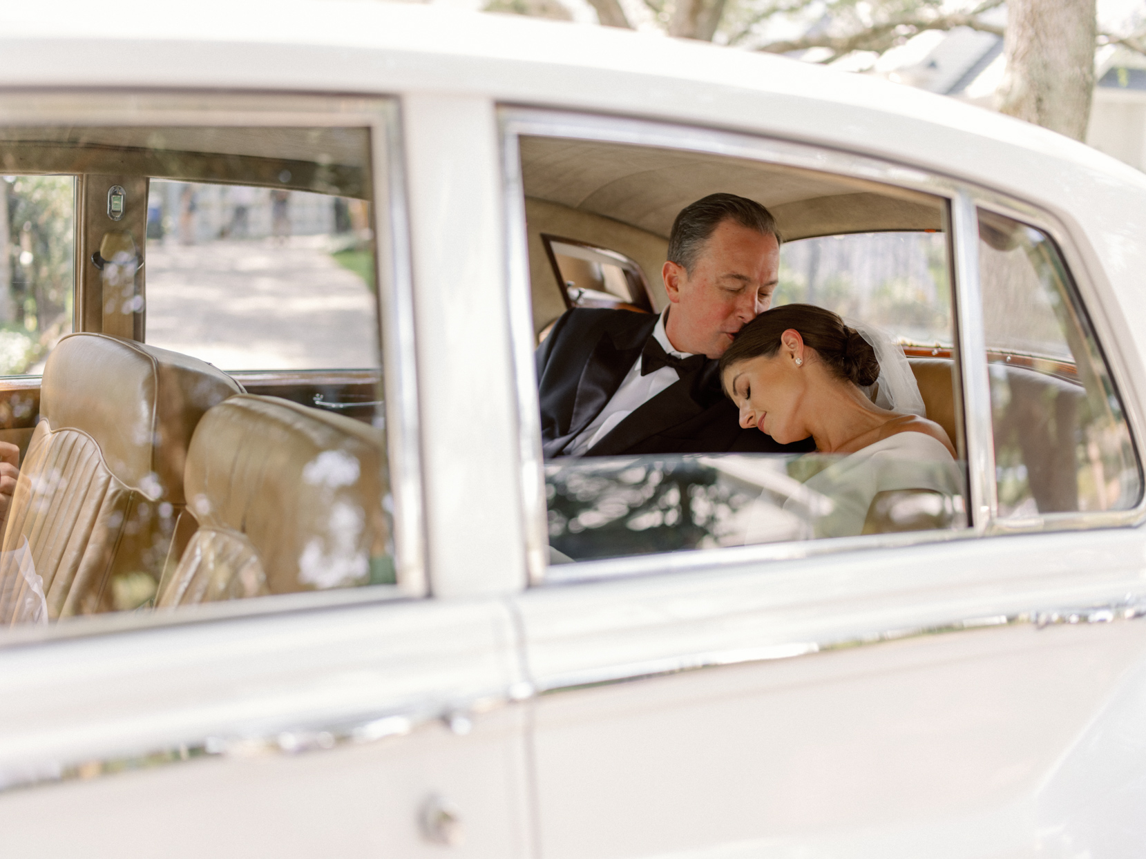 dad kissing bride on top of her head sitting in the back of white vintage car