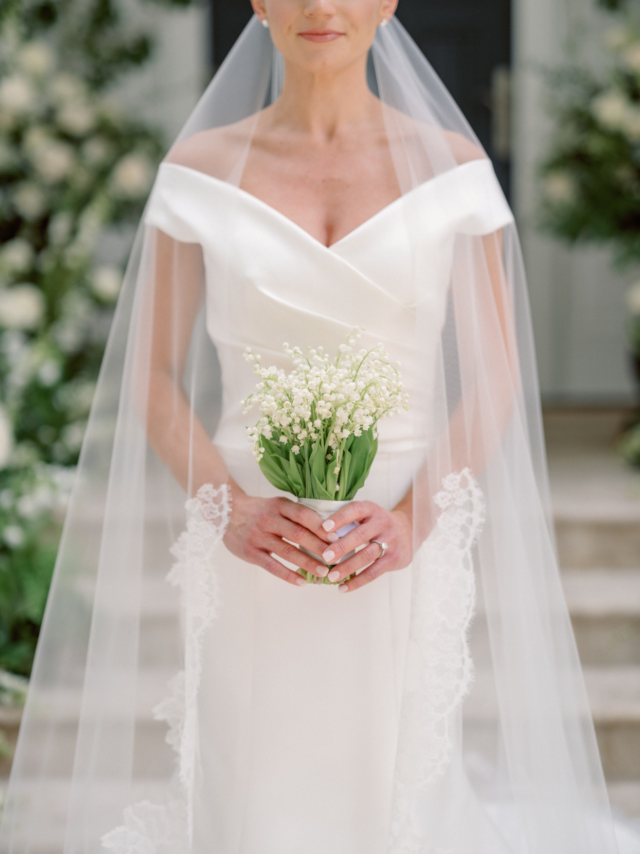 bride wearing off the shoulder dress with long white veil holding white lily of the valley bouquet