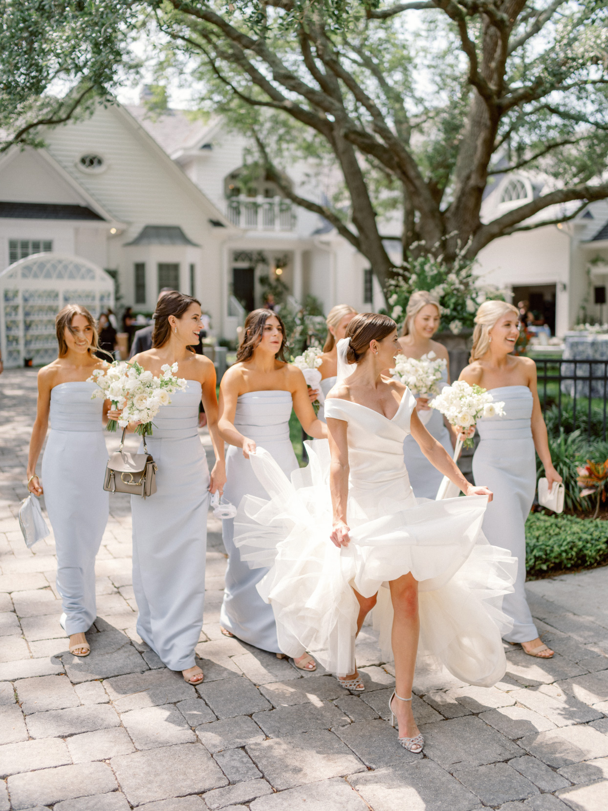bridesmaids wearing pale blue dresses walking with bride
